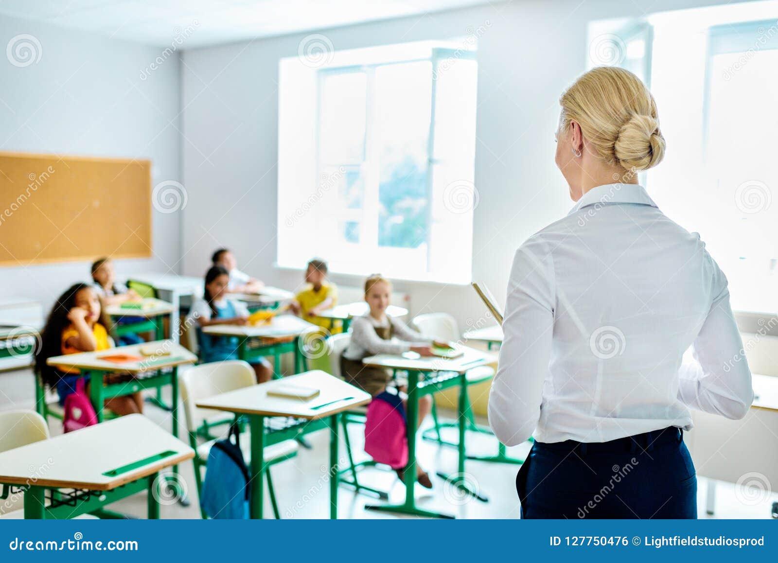 Vue arrière de professeur regardant des enfants