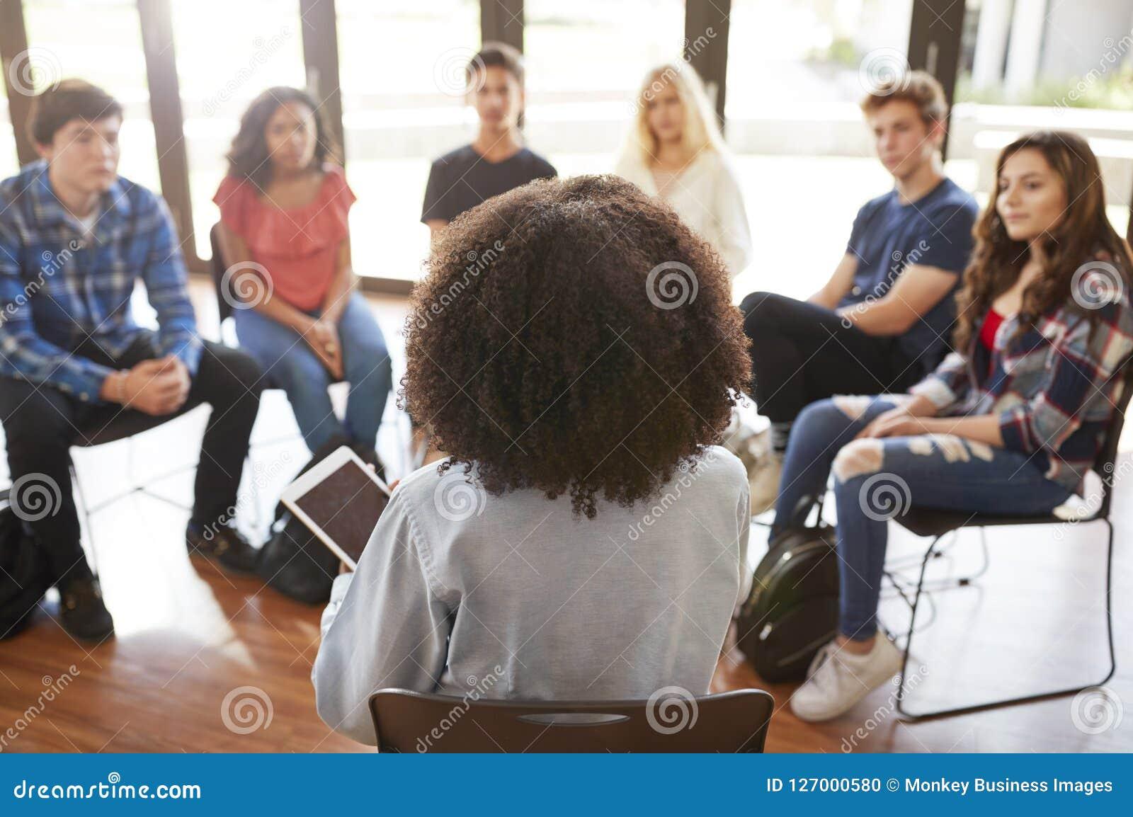 Vue arrière de tuteur féminin Leading Discussion Group parmi des élèves de lycée
