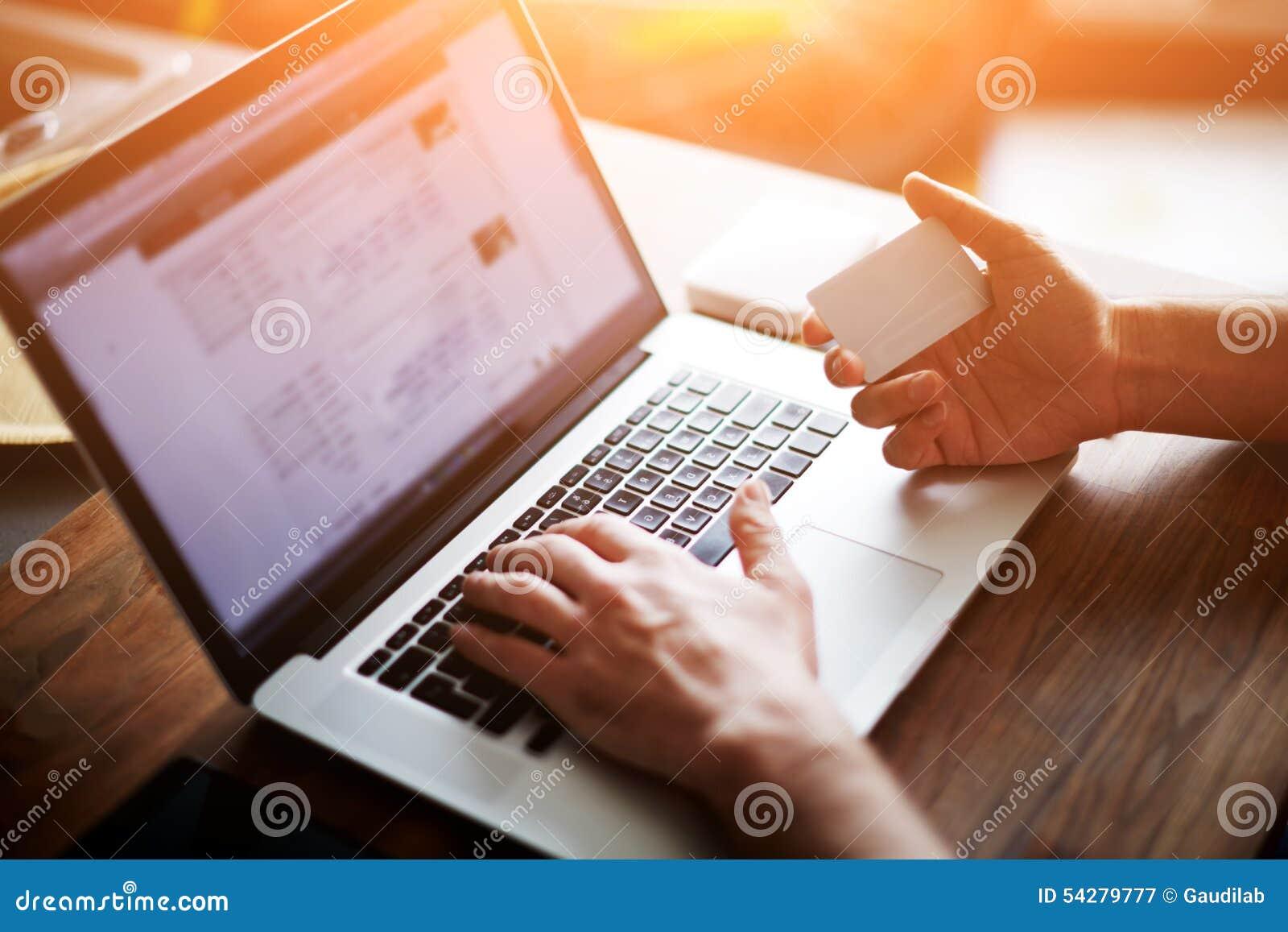 Vue arrière des mains masculines tenant des nombres de dactylographie de carte de crédit sur l ordinateur portable tout en se rep