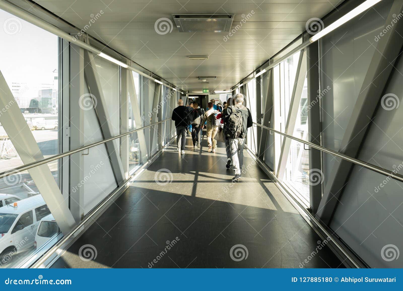 Vue arrière des passagers d une ligne aérienne dans le pont d aéroport, pont en jet où les passagers se relient à l avion Termina