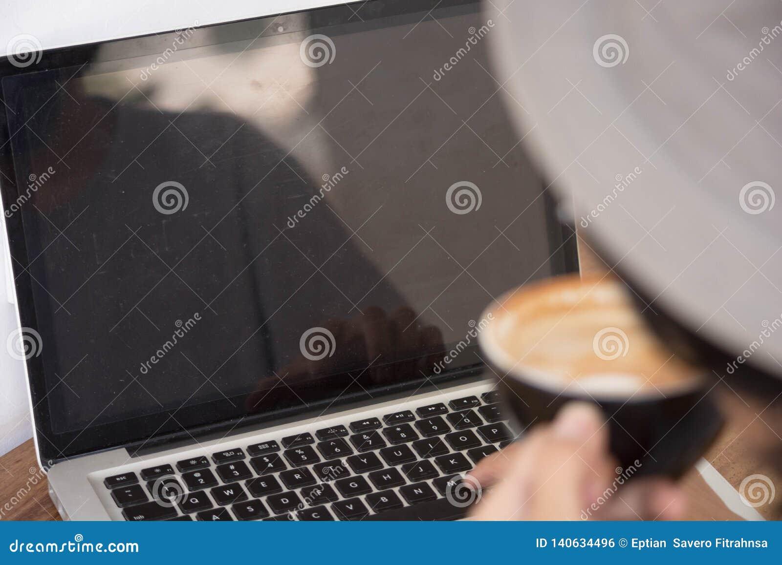 Vue arrière Jeune homme créatif dans la chemise blanche et le chapeau de padora se reposant à la table, utilisant l ordinateur po