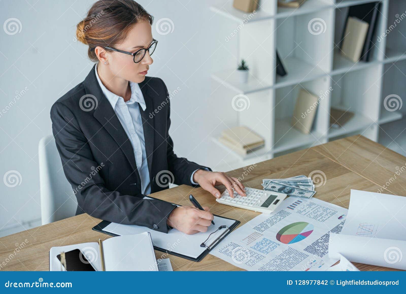Vue courbe de financier travaillant à la table dans le bureau avec la calculatrice