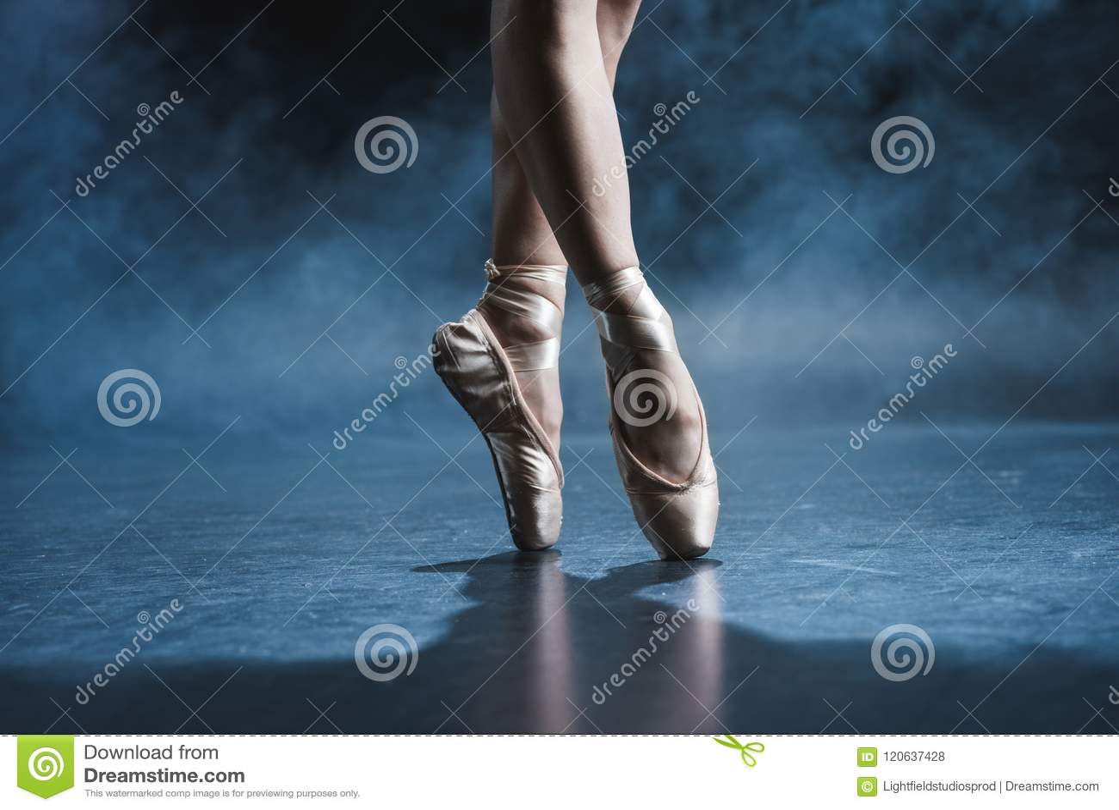 Vue cultivée de danseur classique dans des chaussures de pointe dans le studio foncé