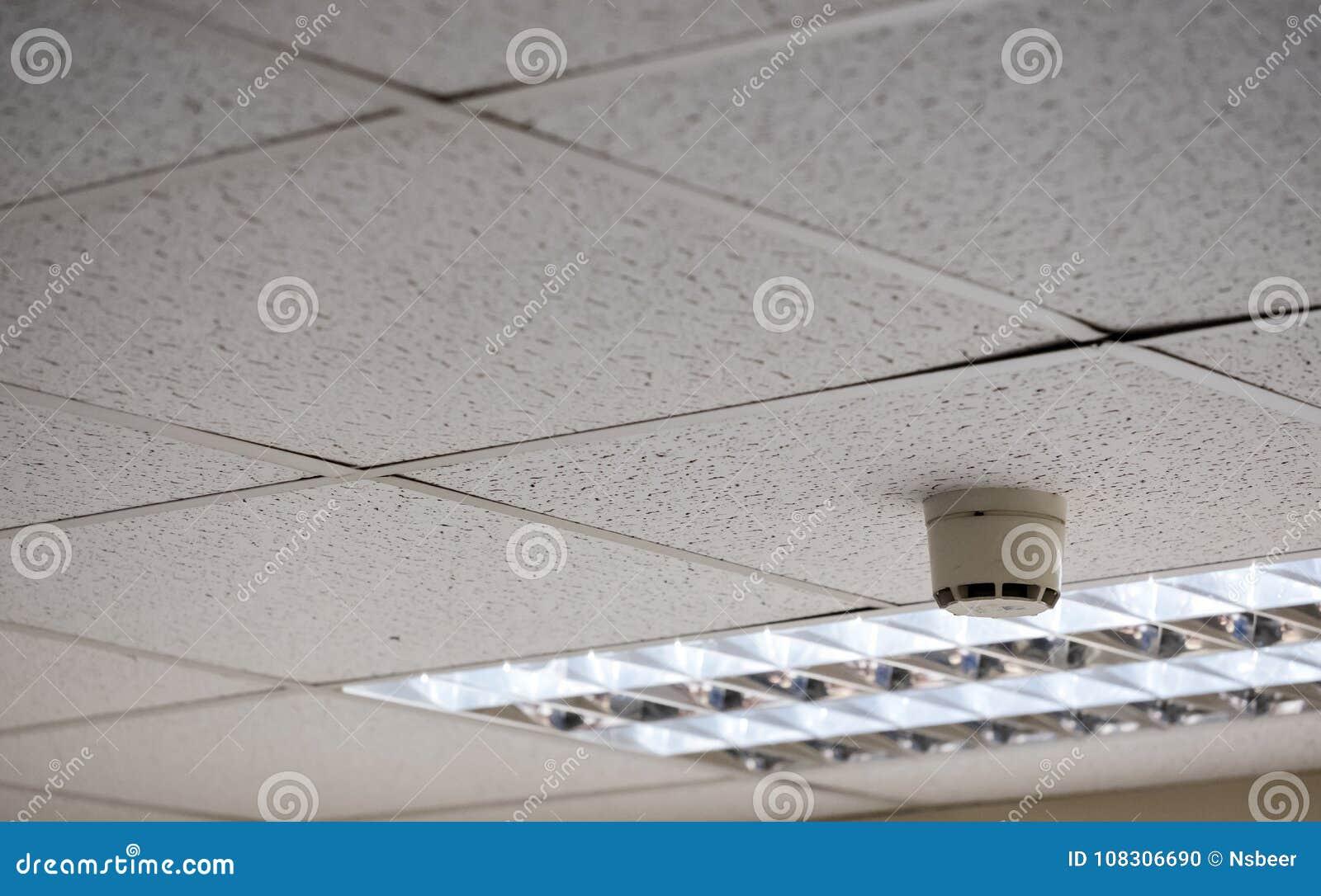 Vue détaillée d un plafond suspendu et d un détecteur de fumée vus