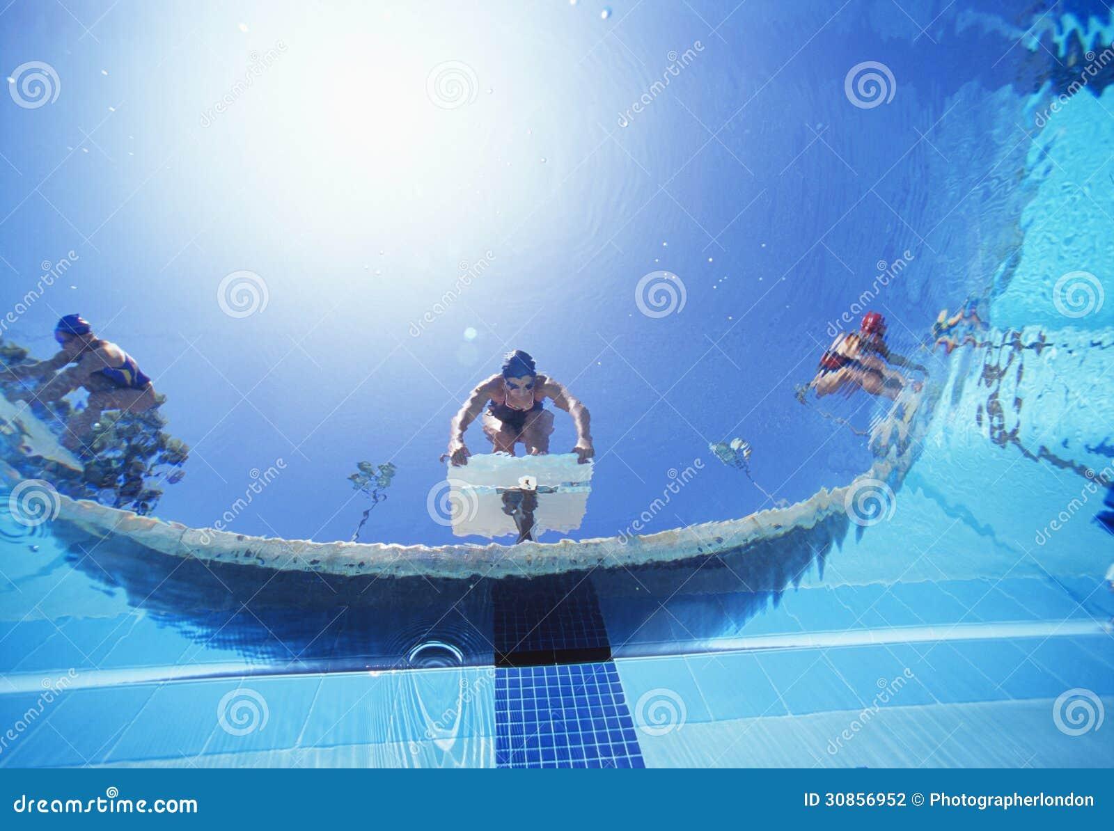 Vue d 39 angle faible des nageurs f minins pr ts plonger for Apprendre a plonger dans la piscine