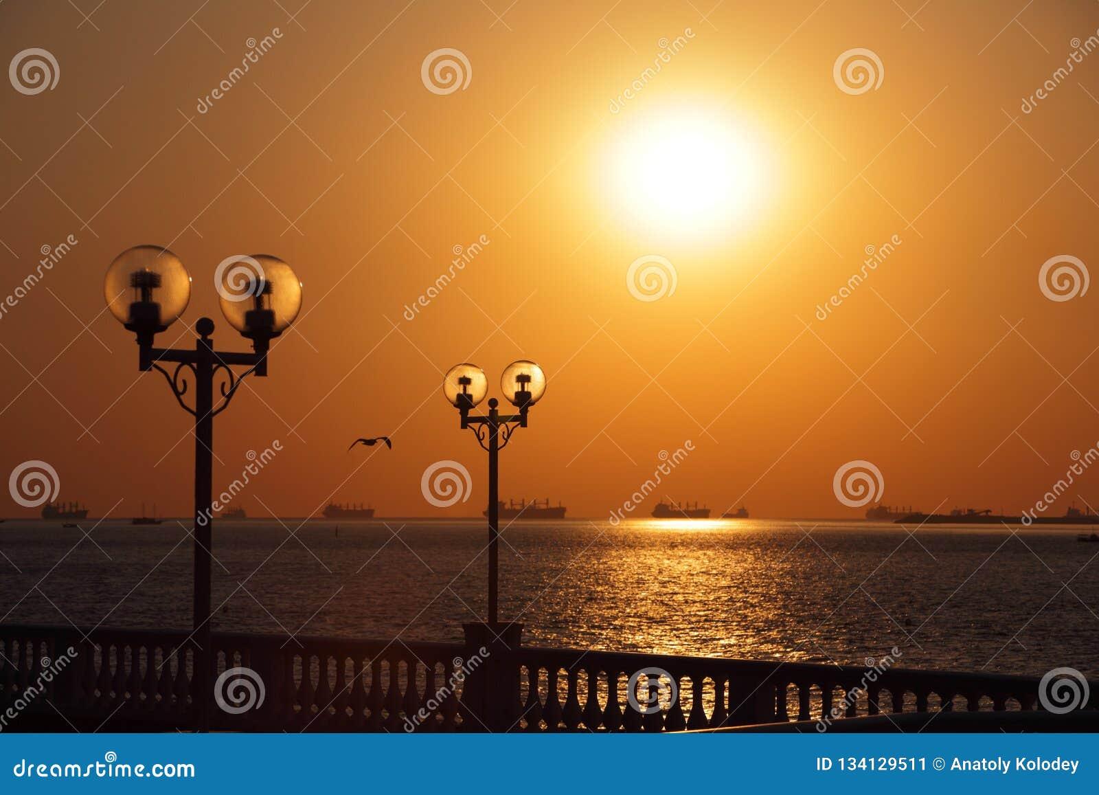 Vue de bord de mer avec des lanternes éclairées à contre-jour par le coucher de soleil et avec des bateaux dans le roadstead