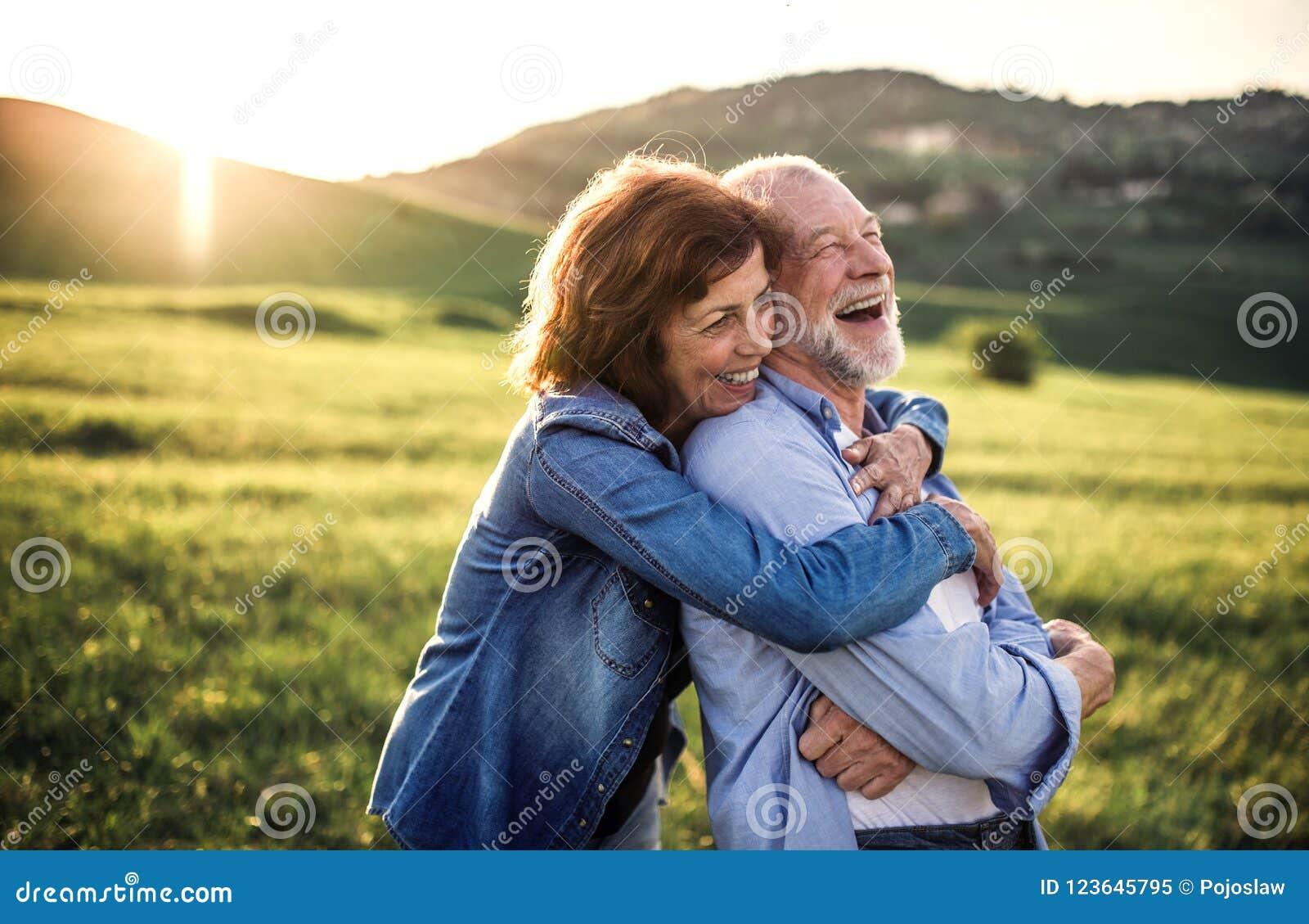 Vue de côté des couples supérieurs étreignant la nature d extérieur au printemps au coucher du soleil