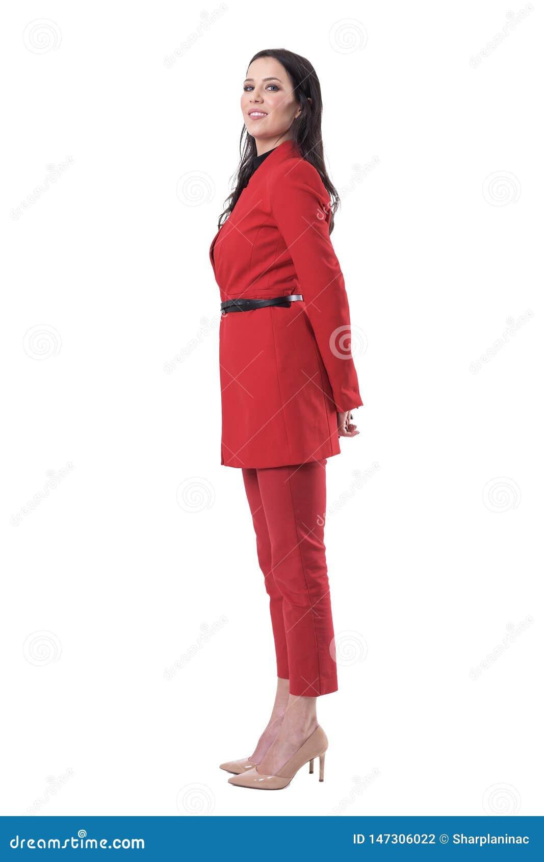 Vue de côté de jeune femme sûre heureuse d affaires dans le costume rouge tournant et regardant la caméra