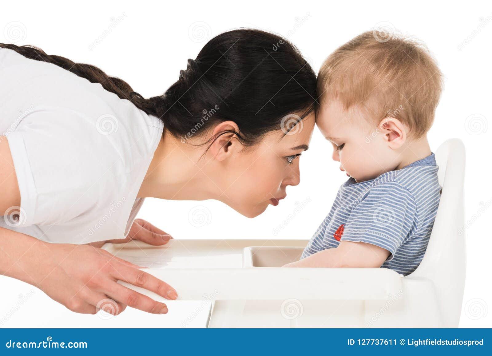 Vue de côté de mère touchant le front de peu de fils s asseyant dans le highchair