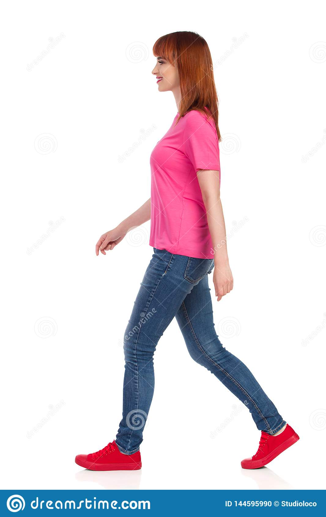 Vue de c?t? de marcher la belle femme dans les espadrilles rouges, les jeans et la chemise rose
