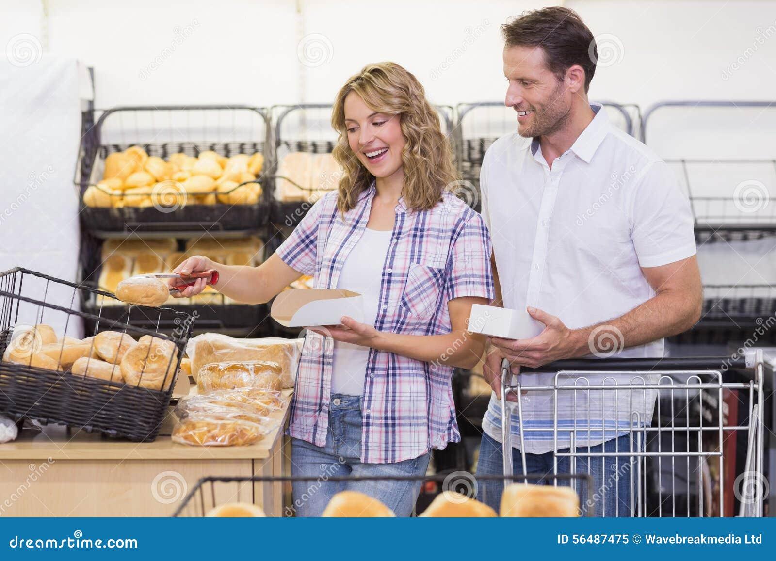 Vue de côté d un couple occasionnel de sourire prenant un pain