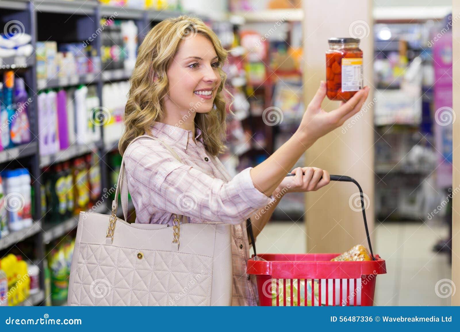 Vue de côté d un sourire femme assez blonde regardant un produit