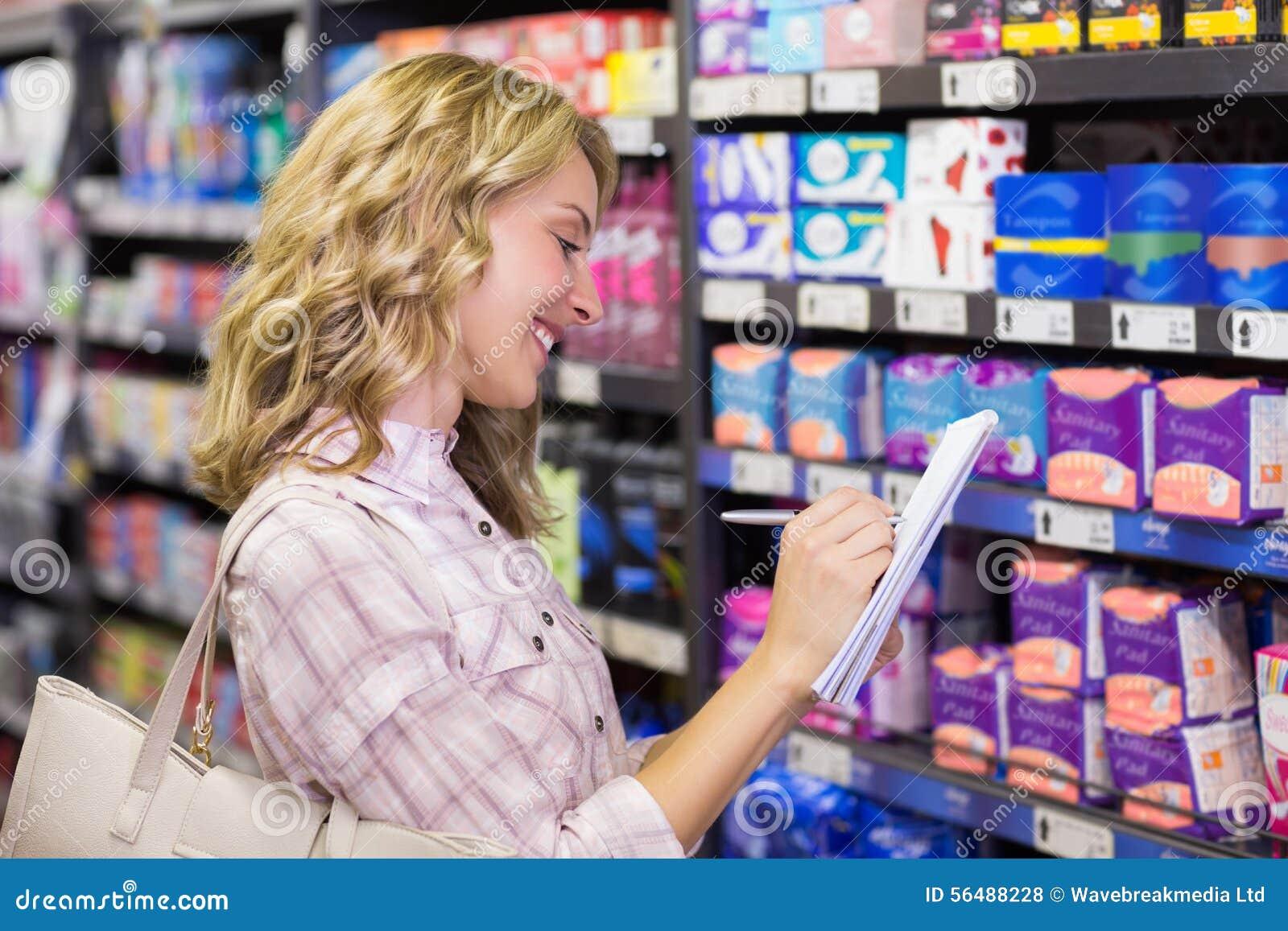 Vue de côté d une écriture blonde de sourire heureuse de femme sur son bloc-notes