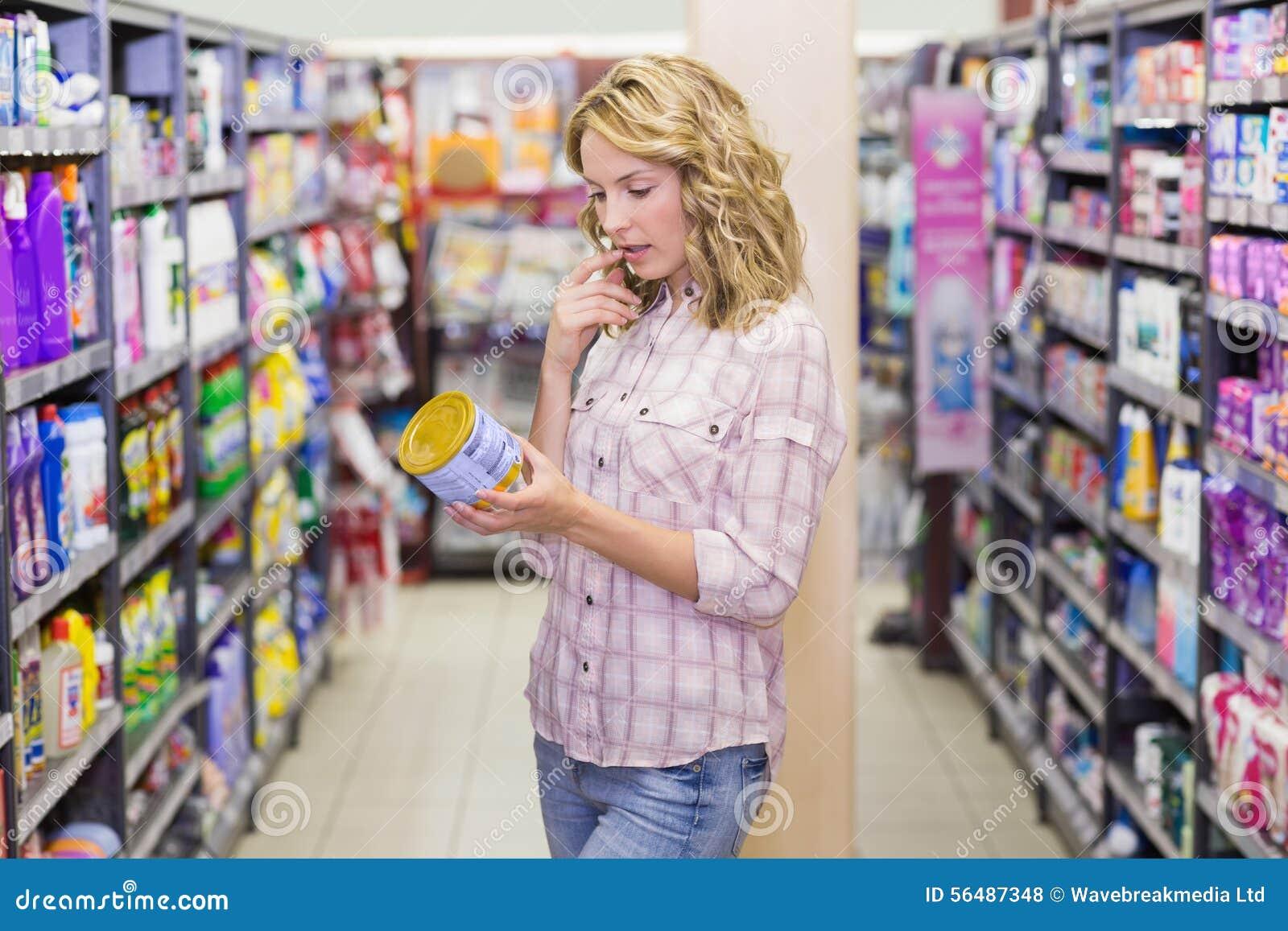 Vue de côté d une femme assez blonde regardant un produit