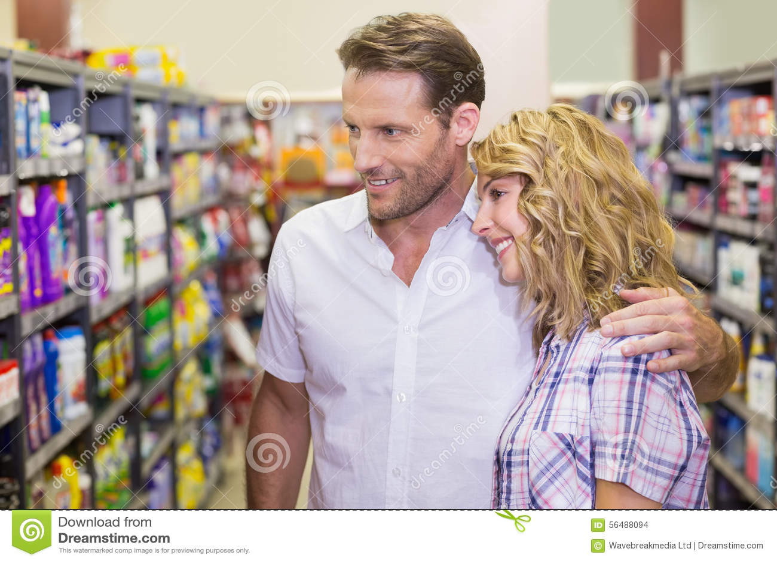 Vue de côté des couples occasionnels de sourire regardant l étagère