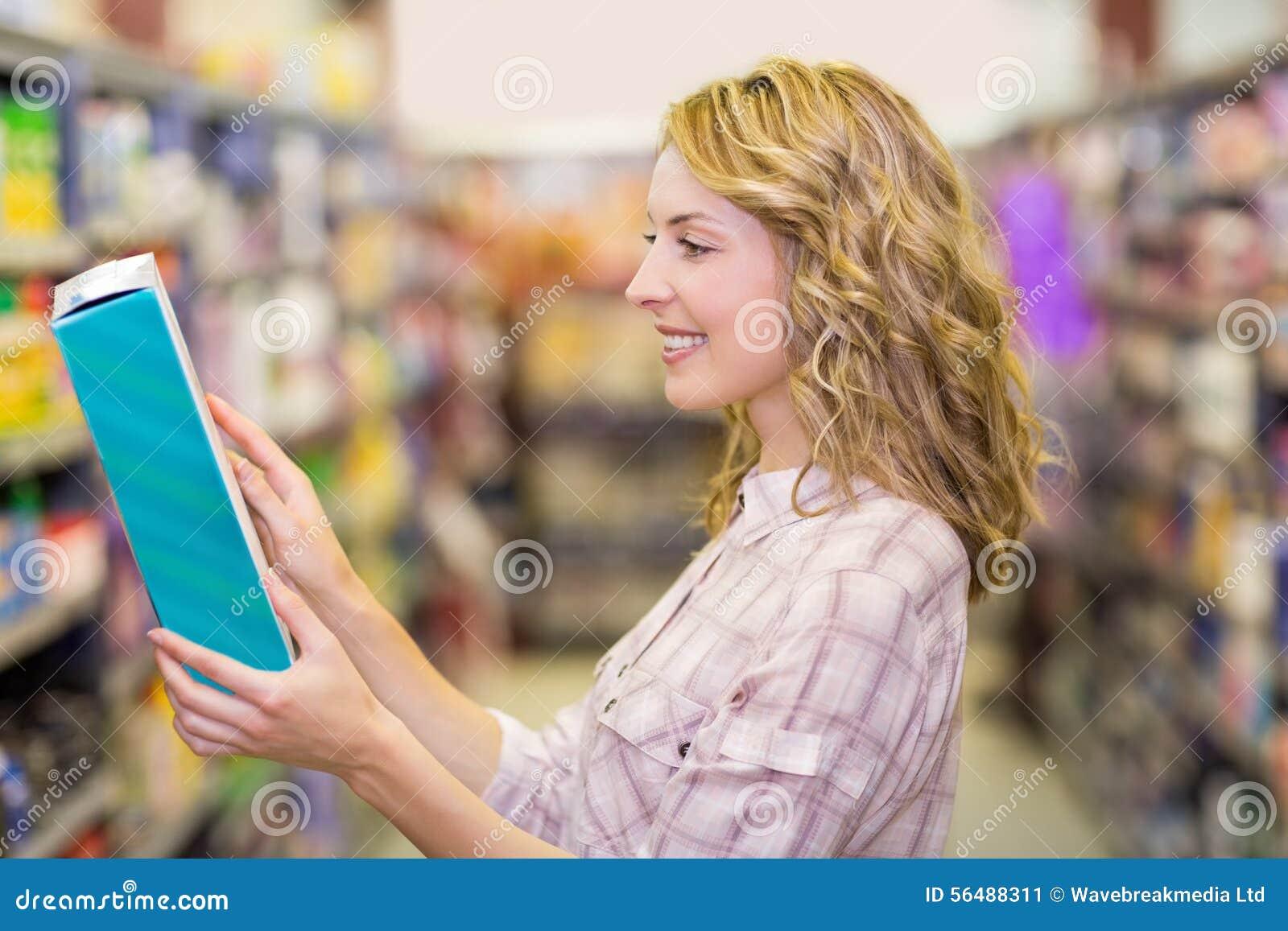 Vue de côté du sourire femme assez blonde lisant un livre