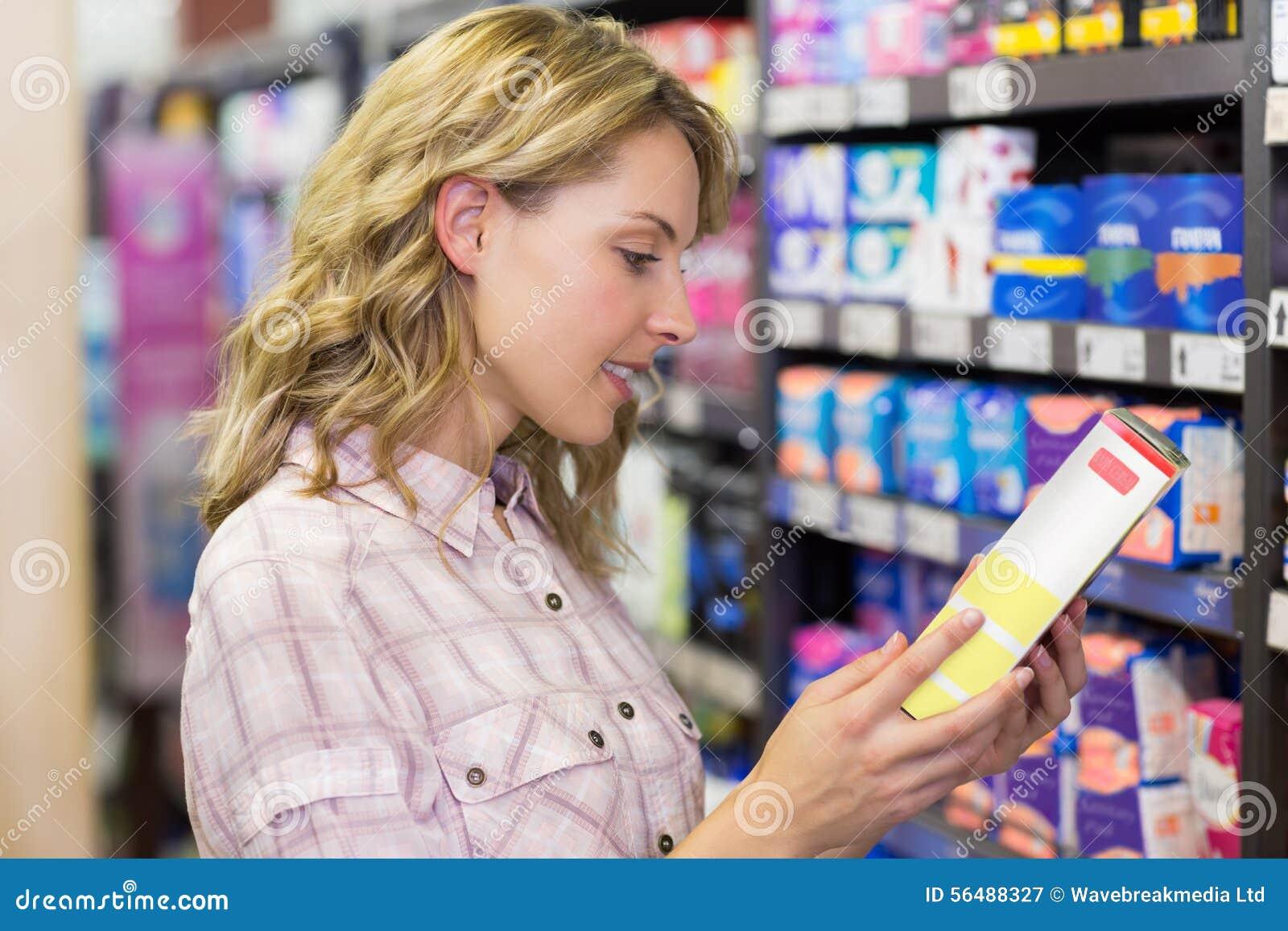 Vue de côté du sourire femme assez blonde regardant un produit