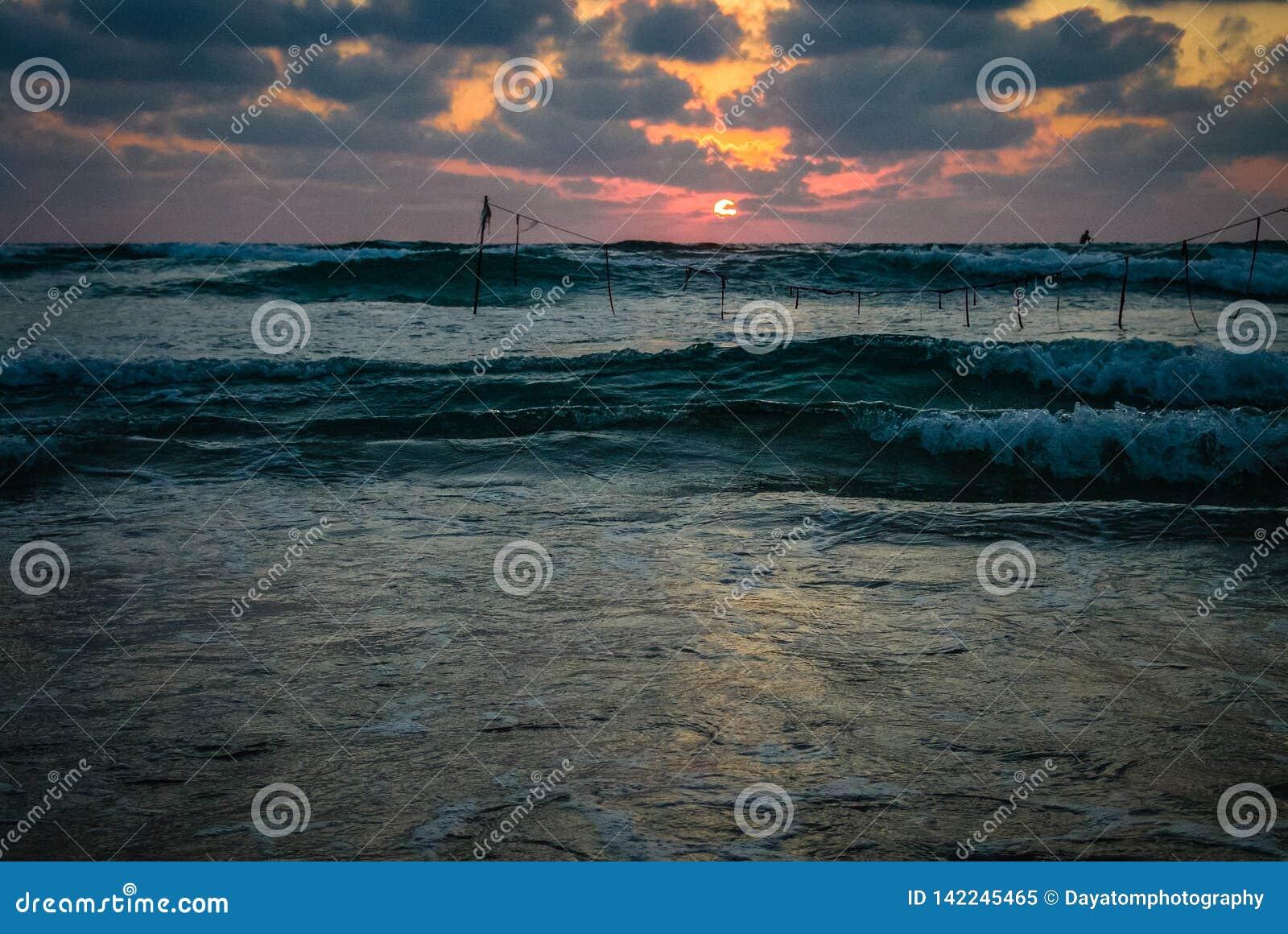 Vue de coucher du soleil d été d une plage sous un ciel nuageux dramatique