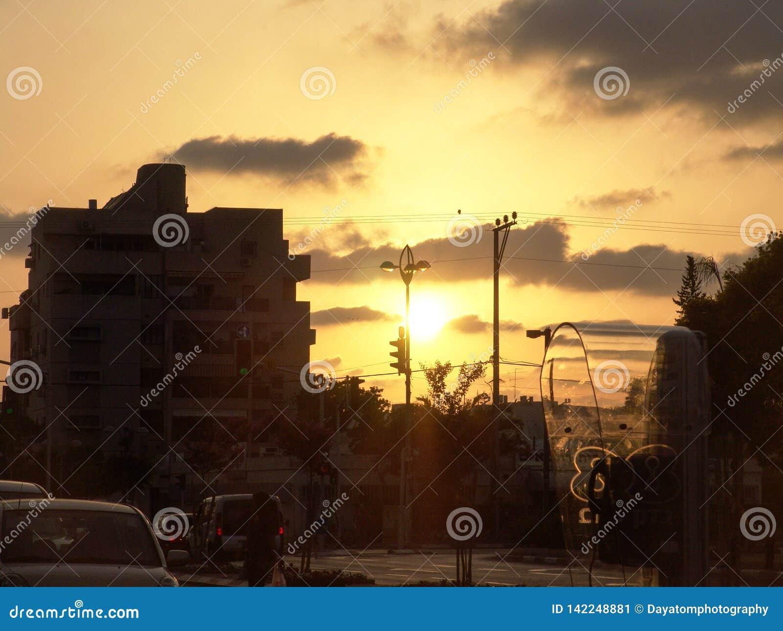 Vue de coucher du soleil d une cabine de téléphone de rue de ville, parking et de vraies personnes sur leur chemin