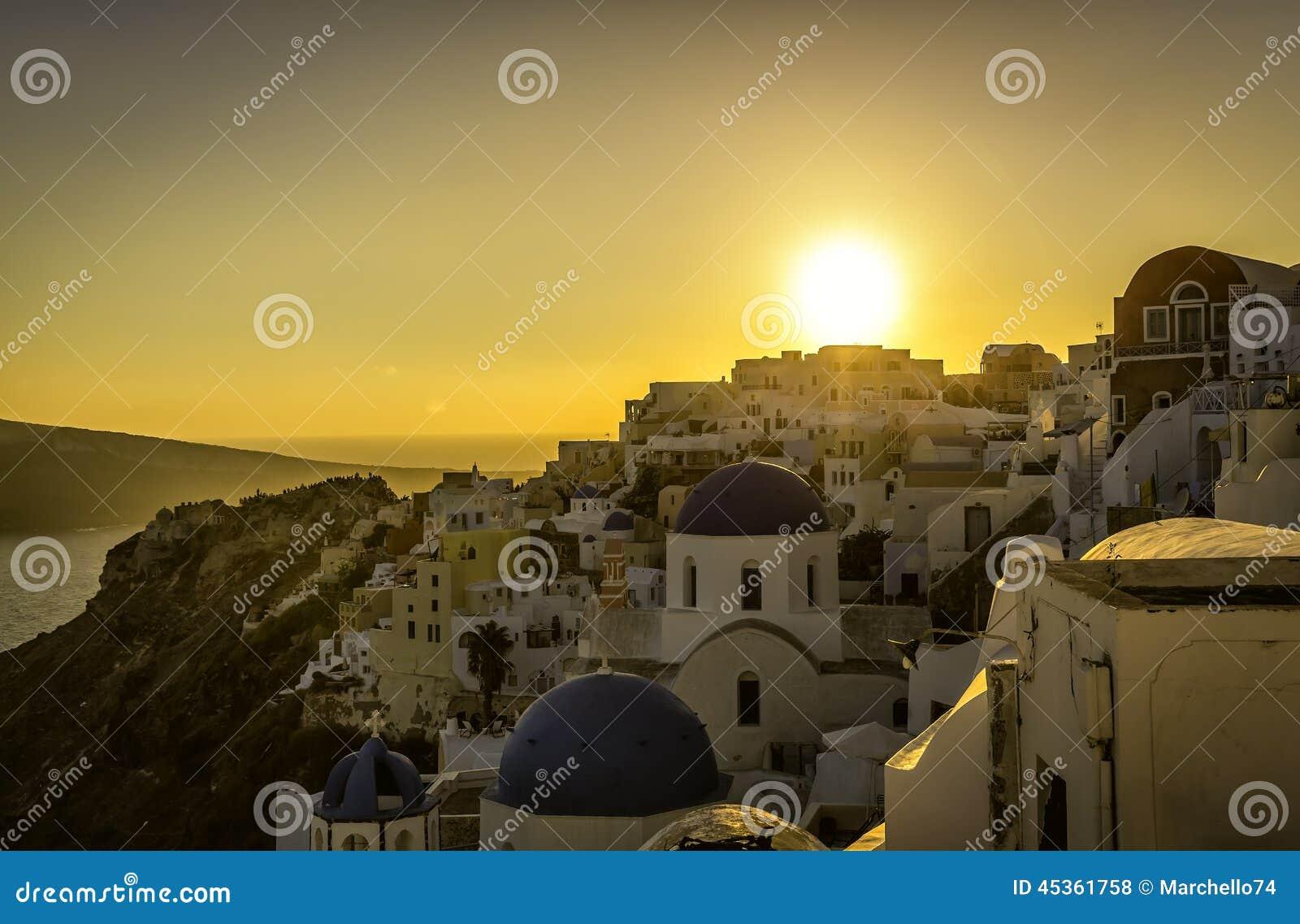 Vue de coucher du soleil des églises bleues de dôme de Santorini