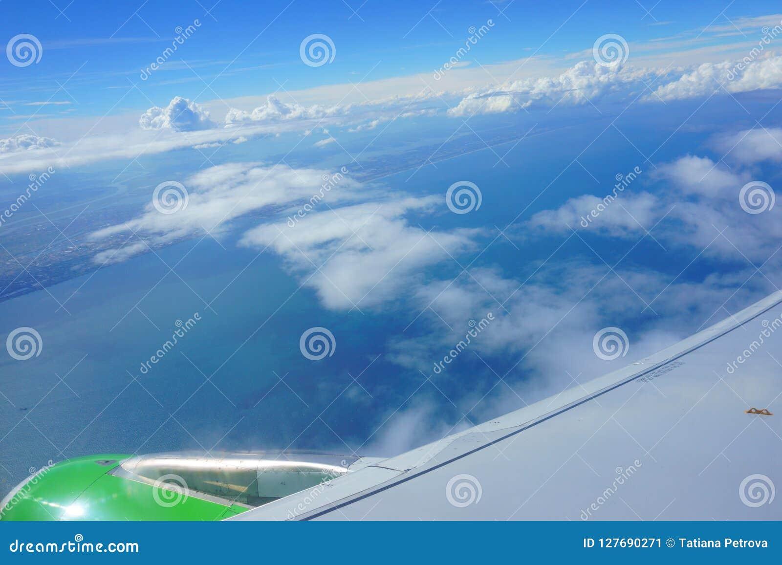 Vue de hublot d avion ciel bleu, mer, côte, aile d avion