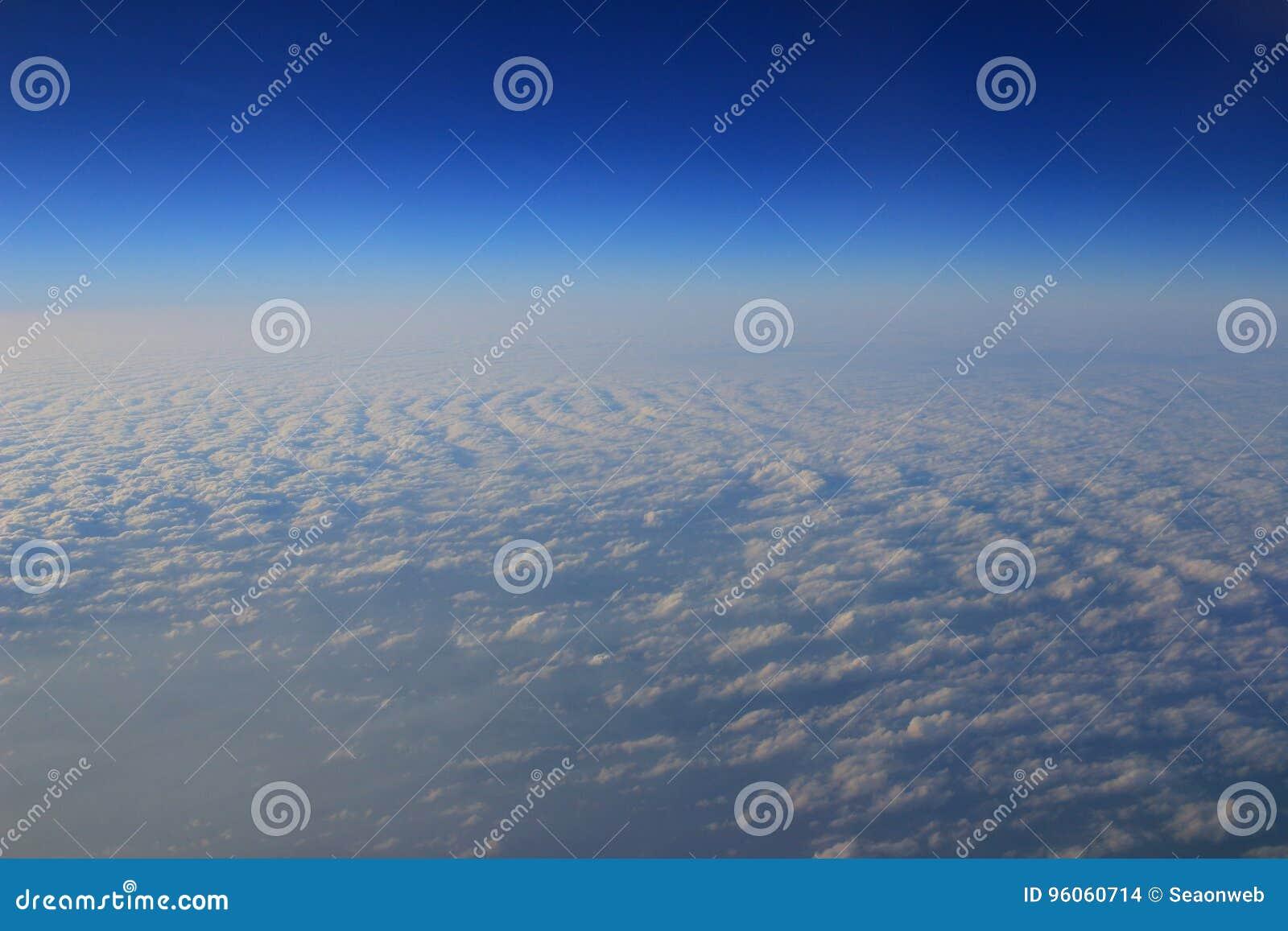 Vue de la fenêtre plate au-dessus du nuage et du ciel bleu