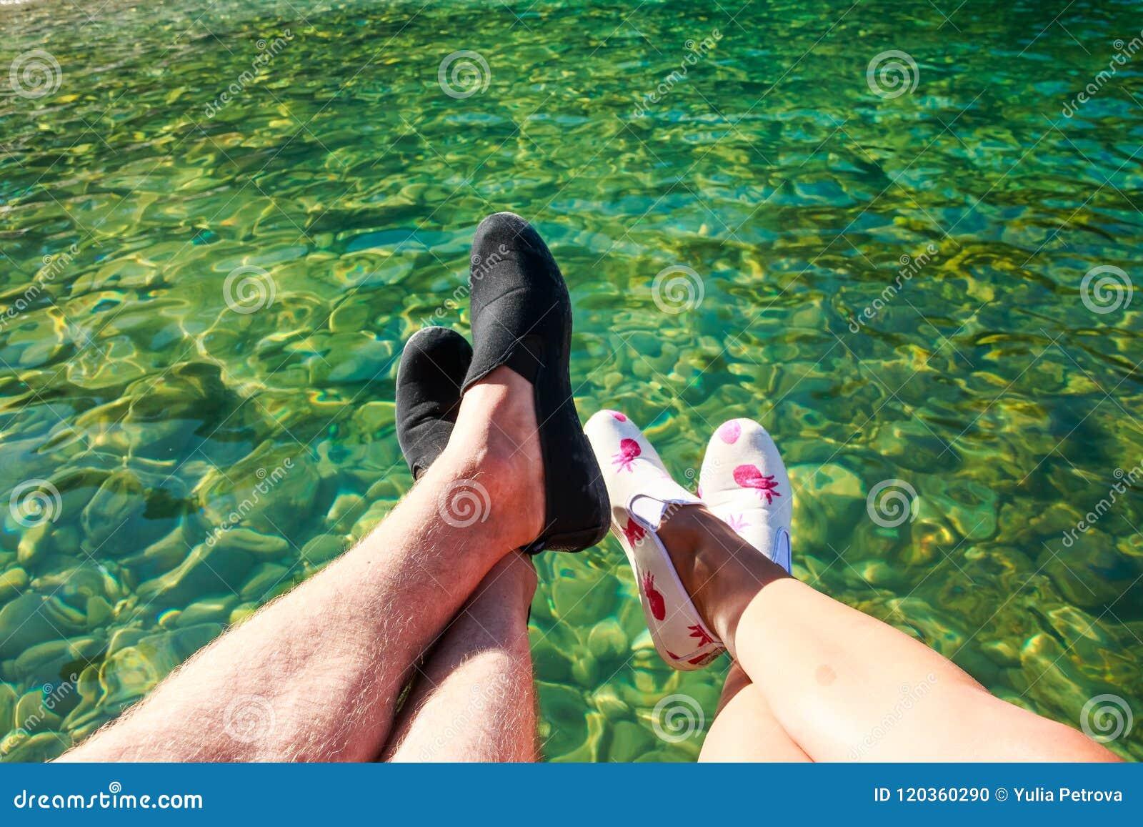 Vue de la première personne sur des pieds de l homme et de la femme s asseyant sur la falaise ou le pilier au-dessus de l eau cla
