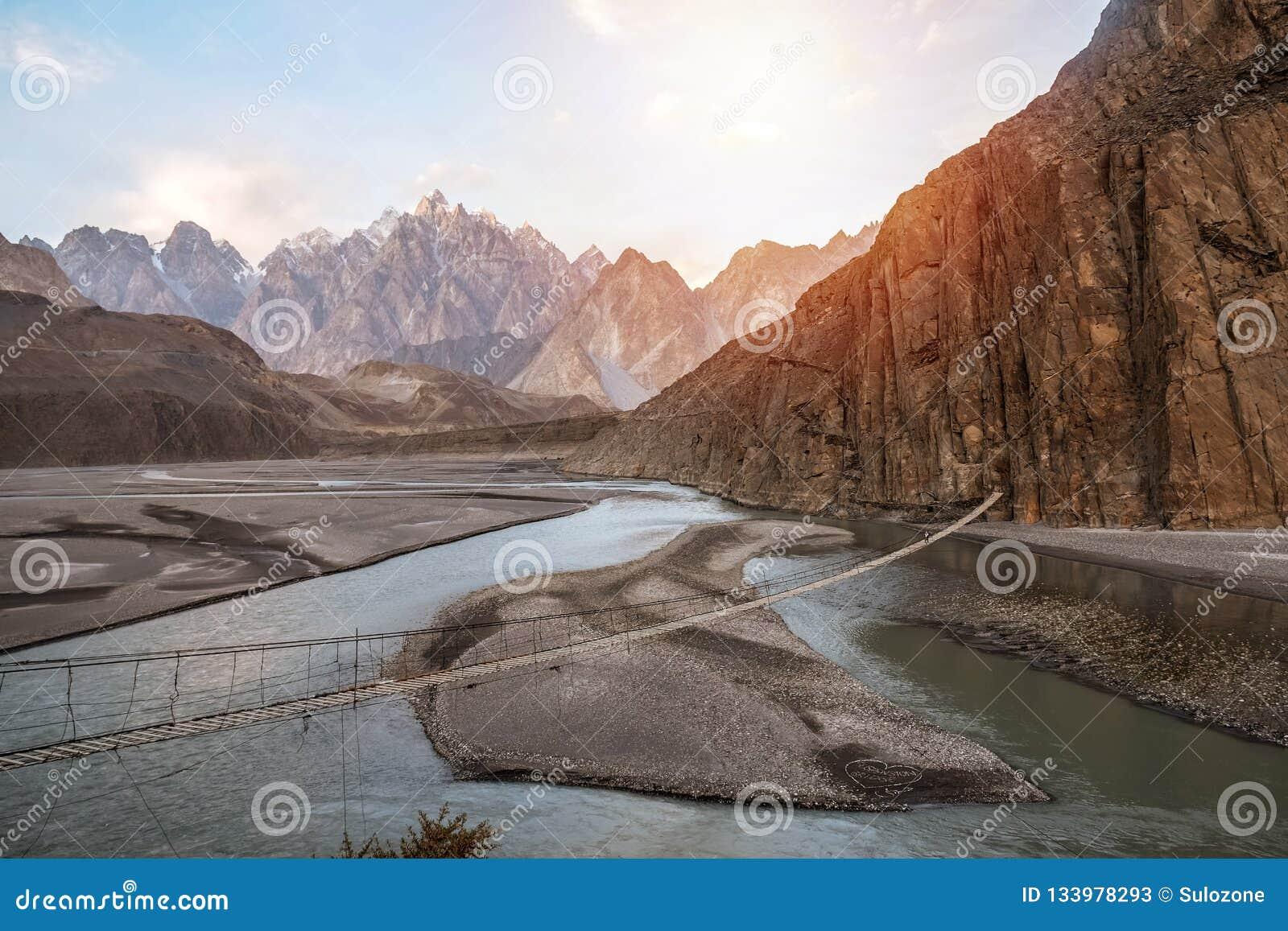 Vue de paysage de pont accrochant de Hussaini au-dessus de rivière de Hunza, entourée par des montagnes pakistan