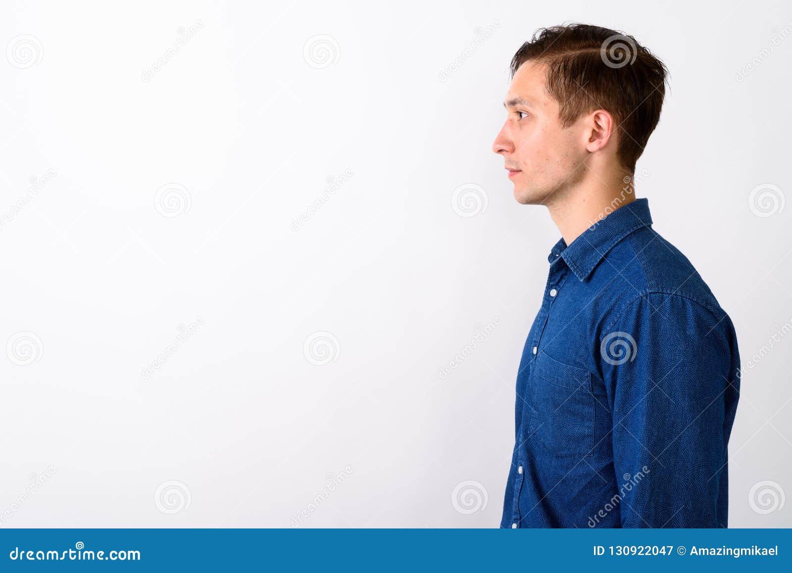 Vue de profil de jeune homme bel sur le fond blanc