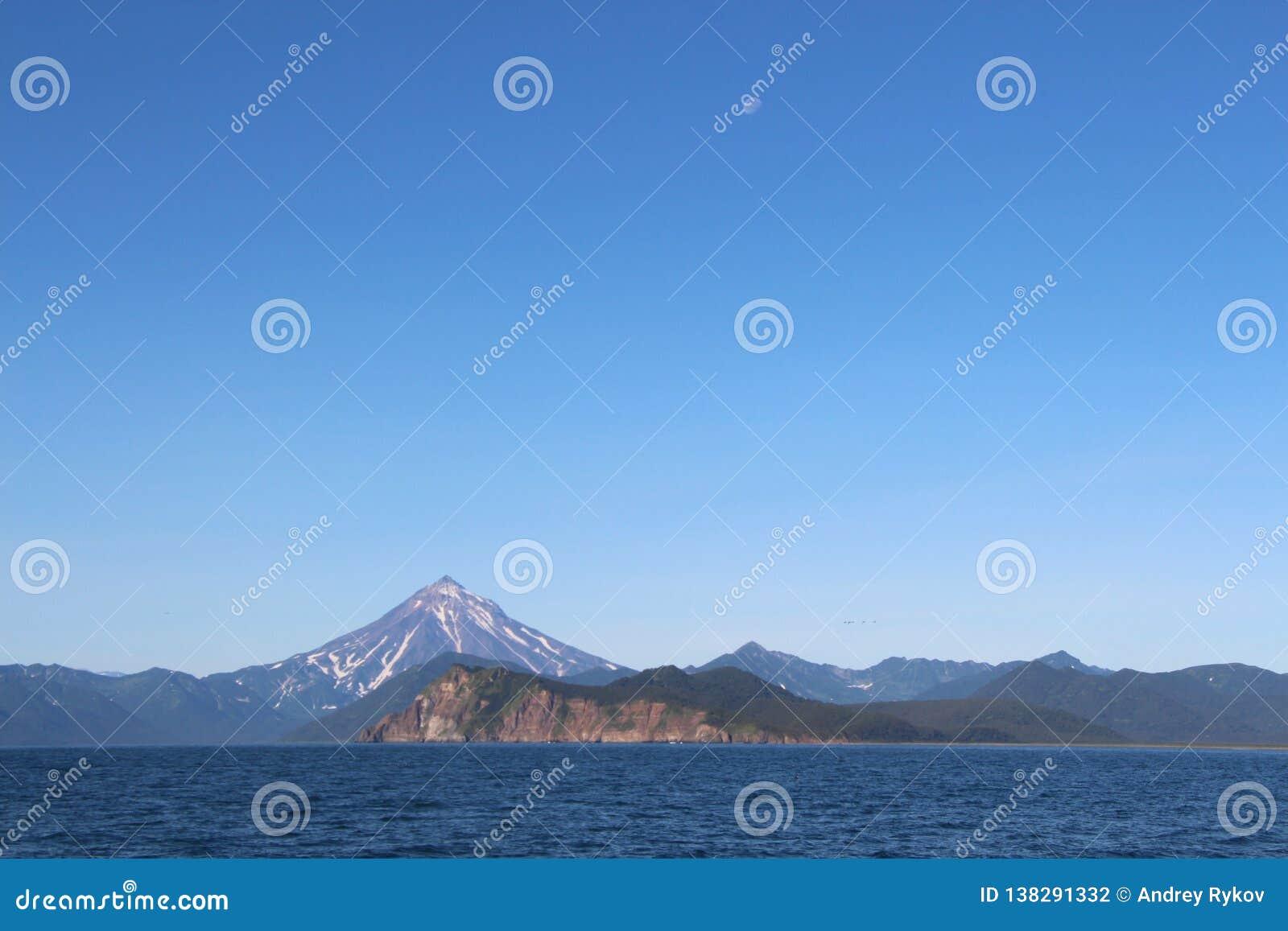 Vue de volcan de Vilyuchinsky et de x28 ; a également appelé Vilyuchik& x29 ; de l eau La lune est évidente dans le ciel