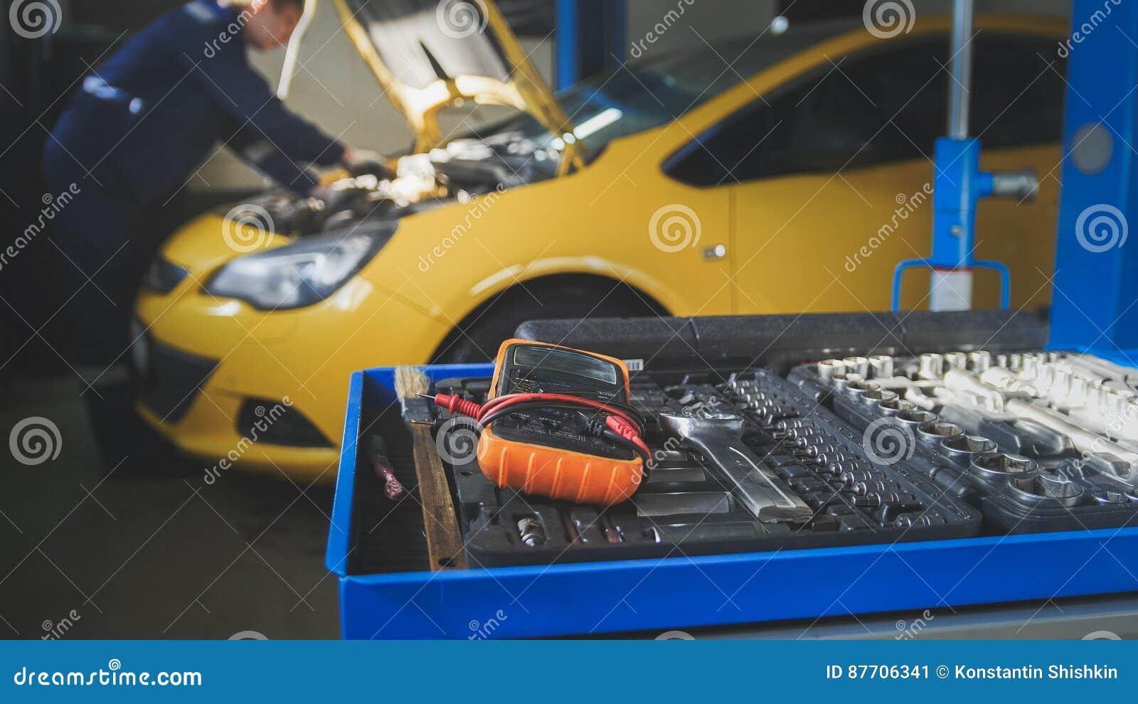 Vue Defocused - mécanicien répare un automobile dévisse le détail de l automobile - service de garage
