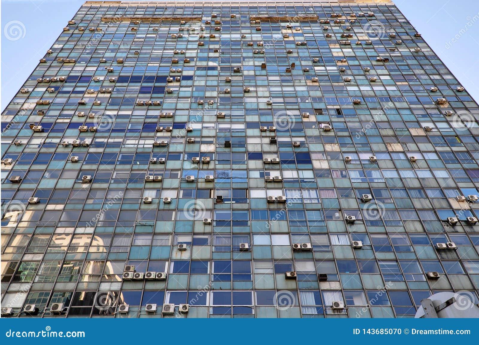 Vue dramatique de vieille façade de construction en verre avec accrocher de dispositifs climatiques