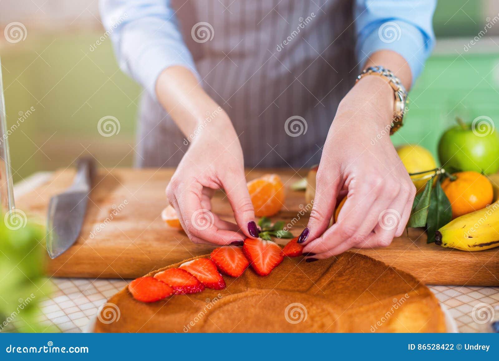 Vue en gros plan des mains femelles mettant la fraise coupée en tranches sur une couche de gâteau Femme faisant le tarte de baie