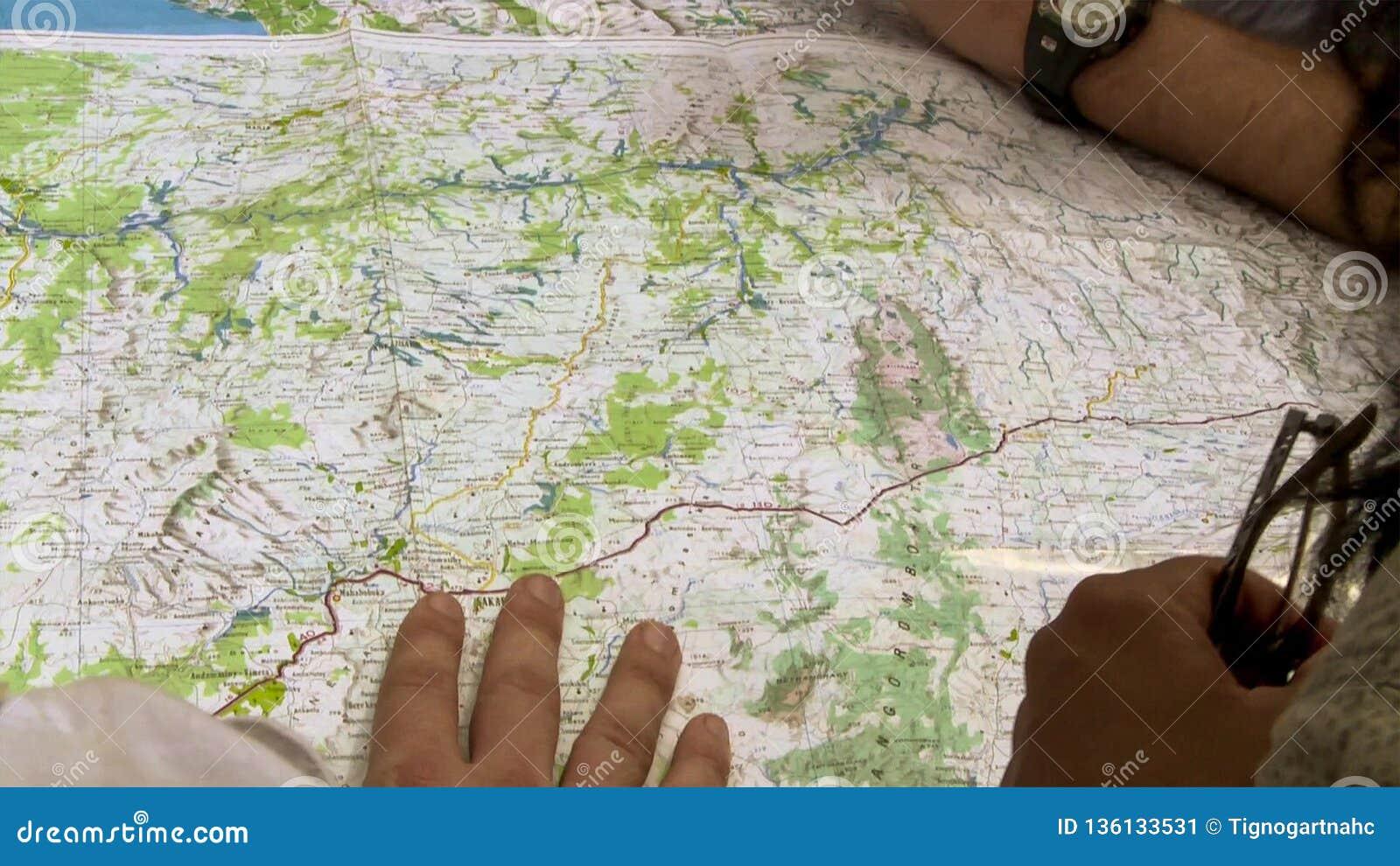 Vue haute étroite de l homme et de la femme se dirigeant aux endroits sur la carte du monde