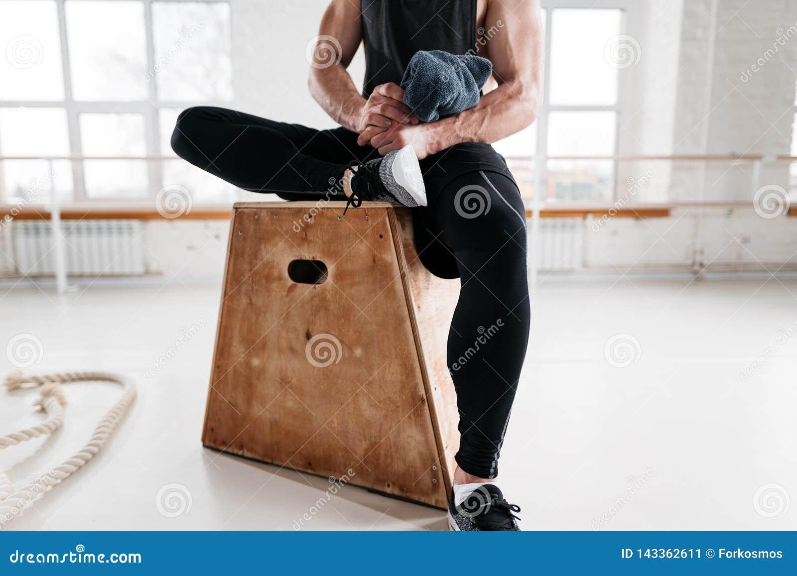 Vue haute étroite sur l athlète masculin fort se reposant sur la boîte en bois après la croix intense dans le gymnase de séance d