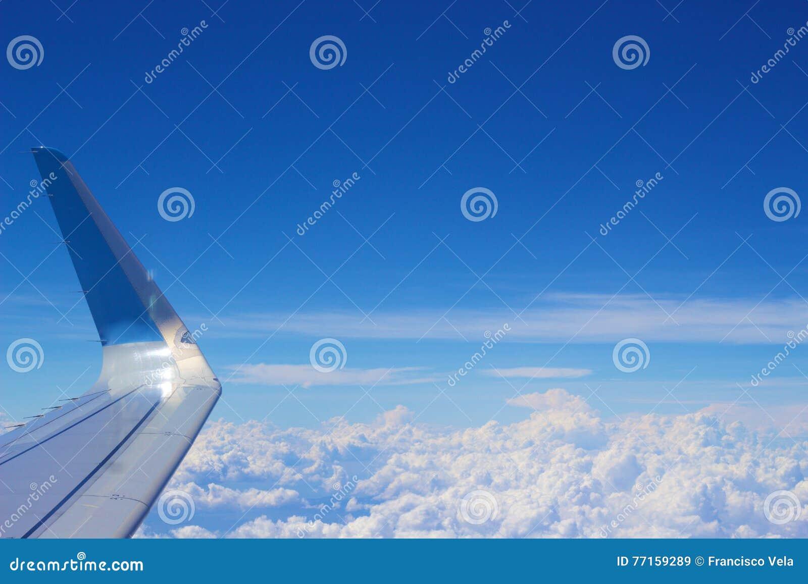 Vue nuageuse claire de ciel bleu avec une aile d avion