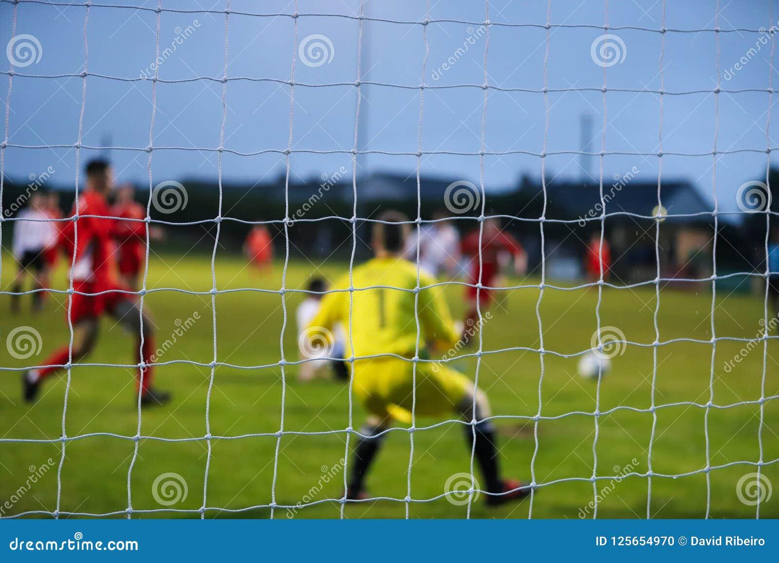 Vue par derrière un but footbal où les joueurs sont hors focale