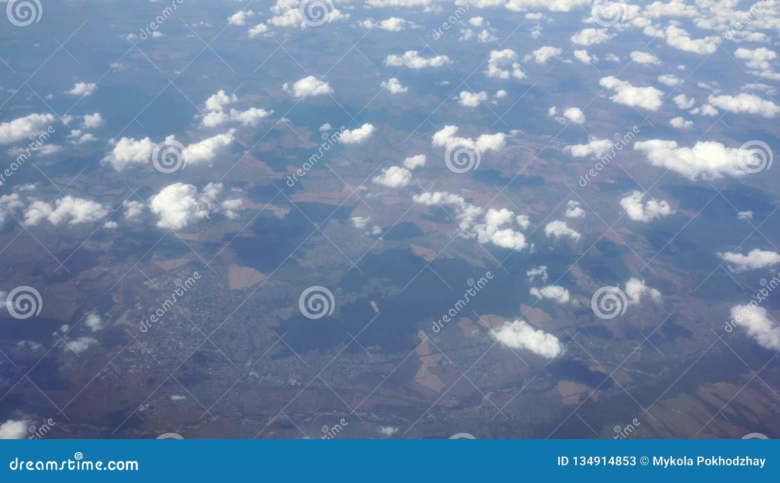 f9b99bb6f7 Déplacement par avion Vue par une fenêtre d'avion de ciel nuageux et d'océan  ci-dessous au lever de soleil