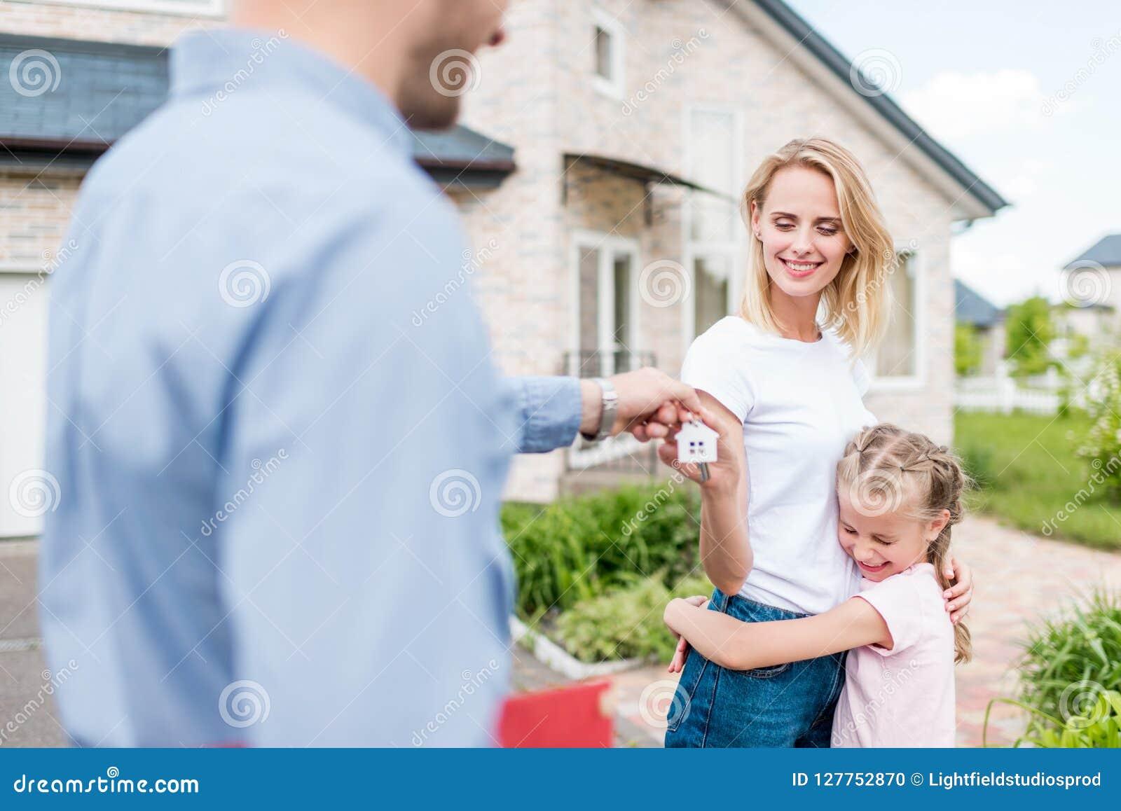 Vue partielle de vrai agent immobilier donnant la clé à la jeune femme
