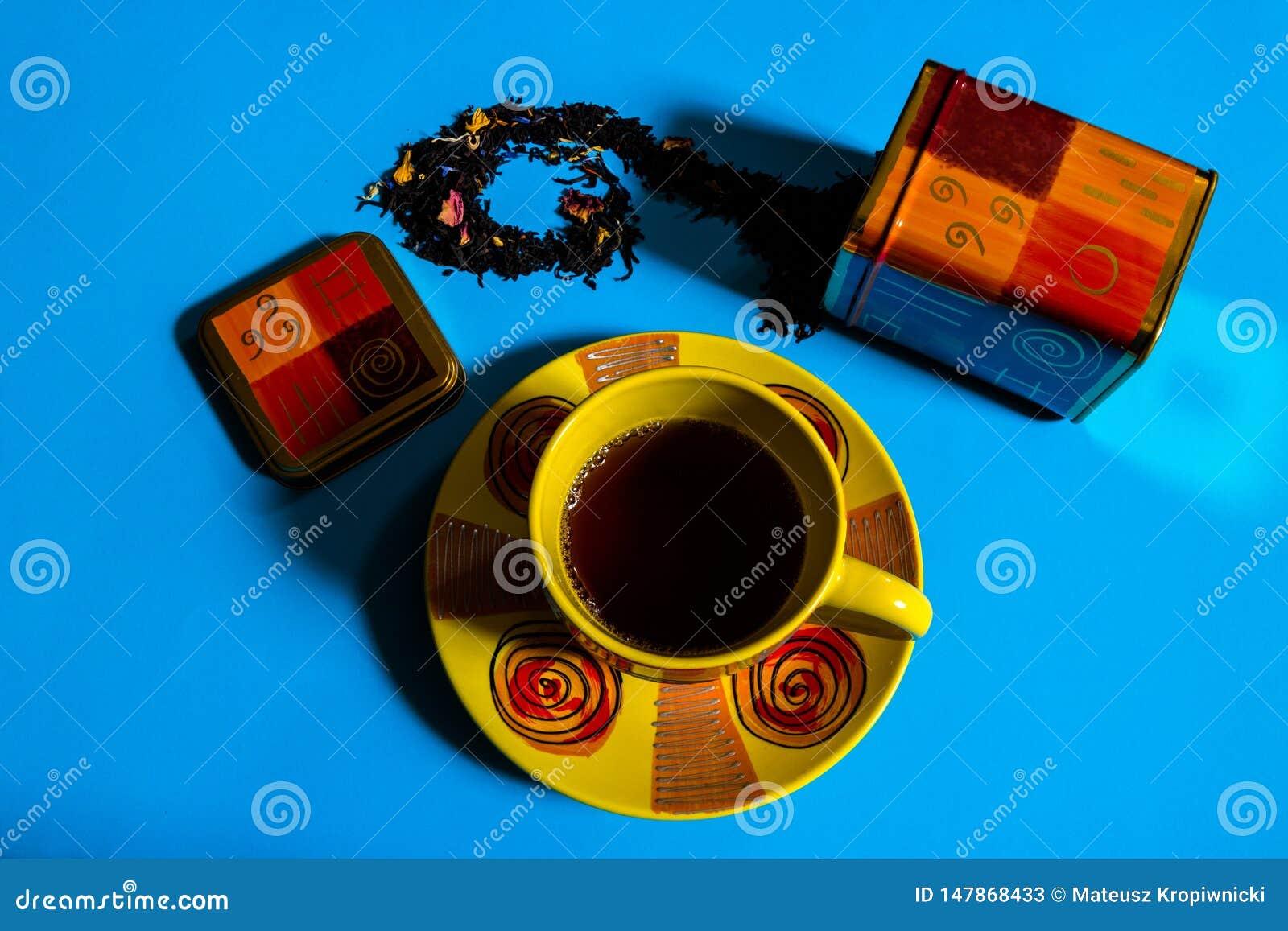 Vue plate de concept de temps de th? avec la tasse de th? color?e, conteneur de th?, th? noir l?che sur le fond bleu