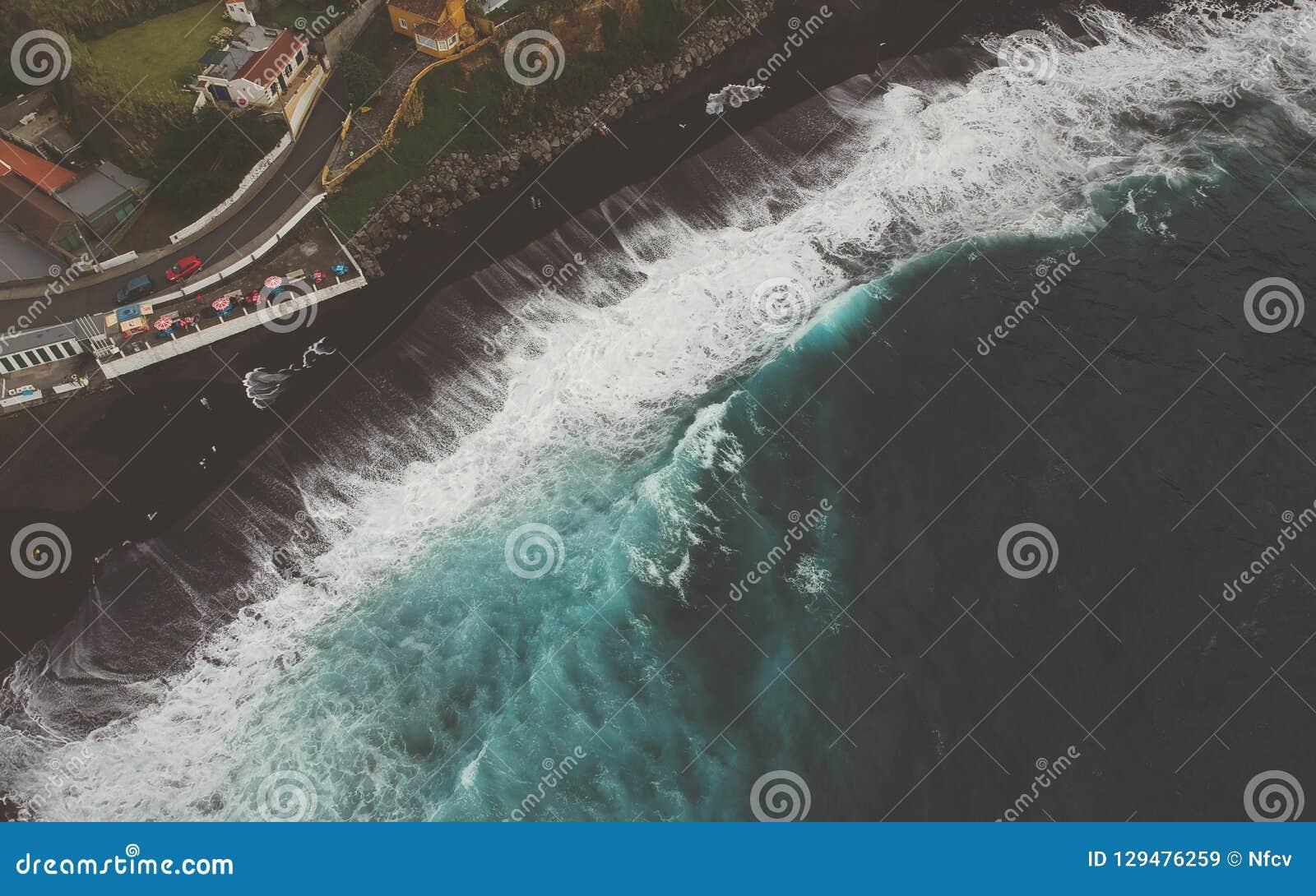 Vue supérieure aérienne des vagues de mer frappant une plage avec le sable volcanique noir avec l eau de mer de turquoise