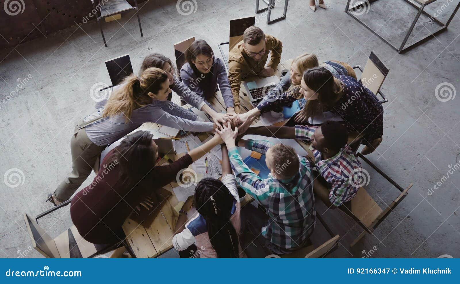 Vue supérieure d équipe d affaires travaillant au bureau à la mode de grenier Le jeune groupe de personnes de métis remonte la pa