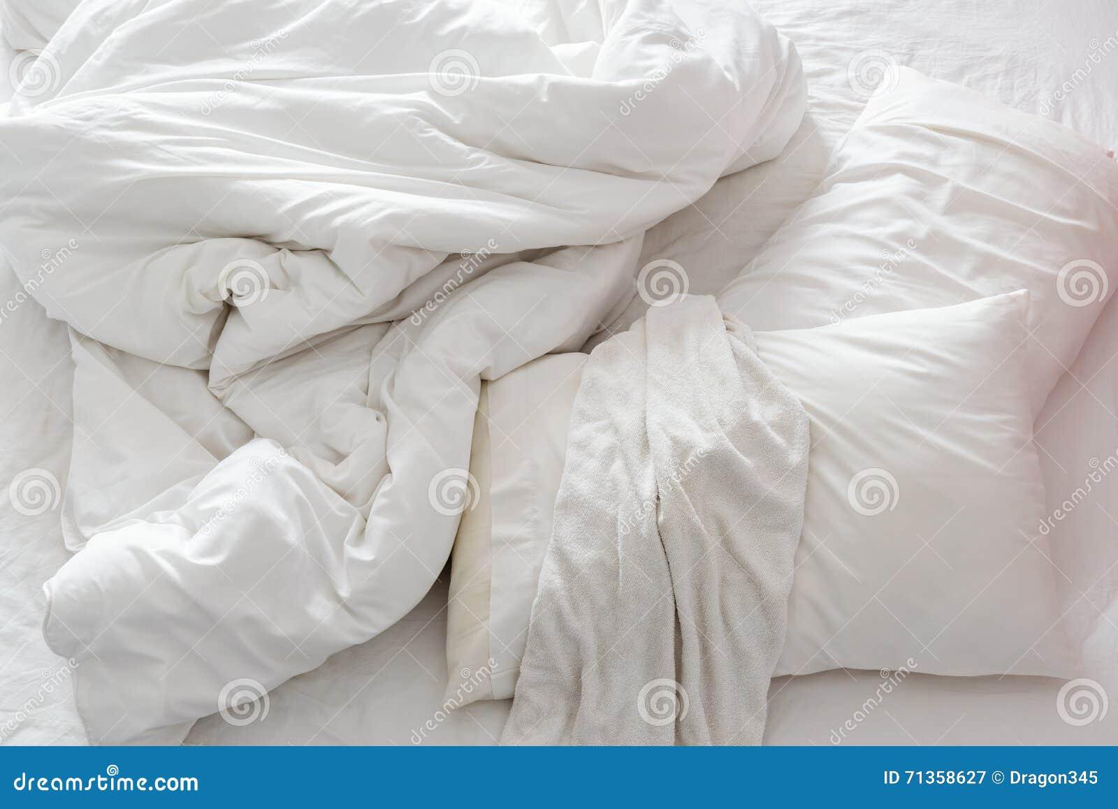 vue sup rieure d 39 un lit qui n 39 est pas encore fait dans une chambre coucher avec le drap. Black Bedroom Furniture Sets. Home Design Ideas