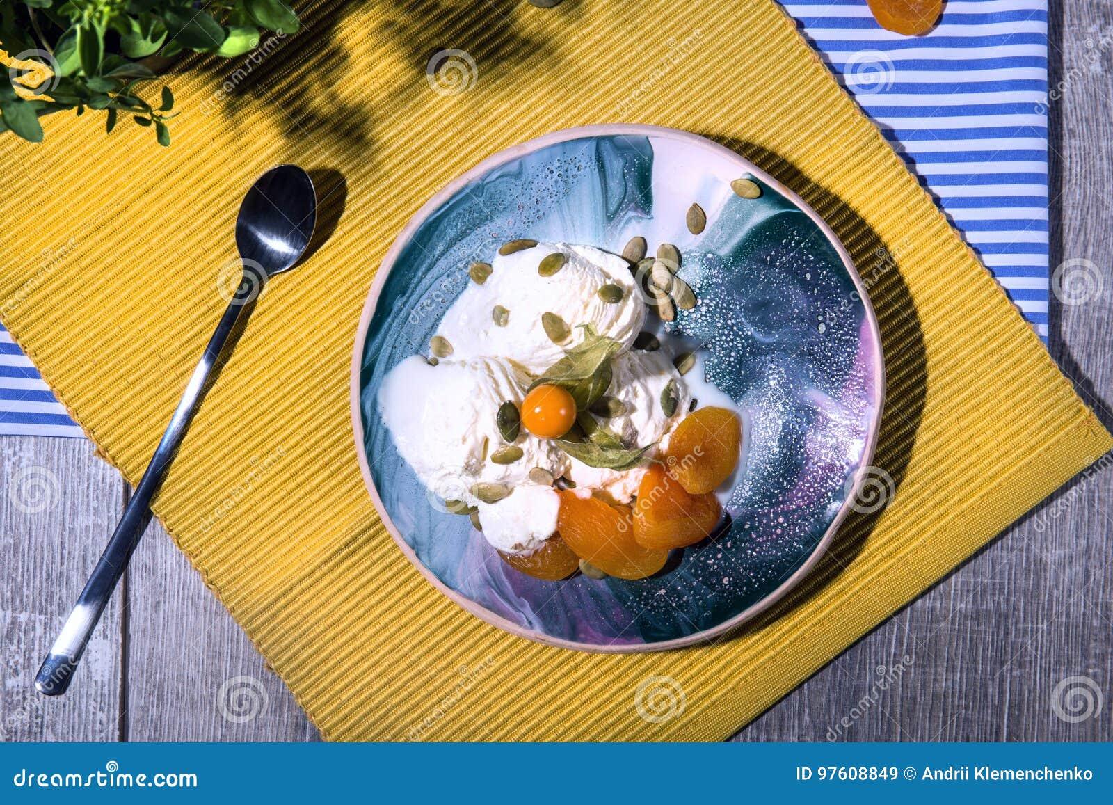 Vue supérieure d une crème glacée blanche de petit déjeuner d été avec des abricots et une cuillère sur un fond lumineux de tissu