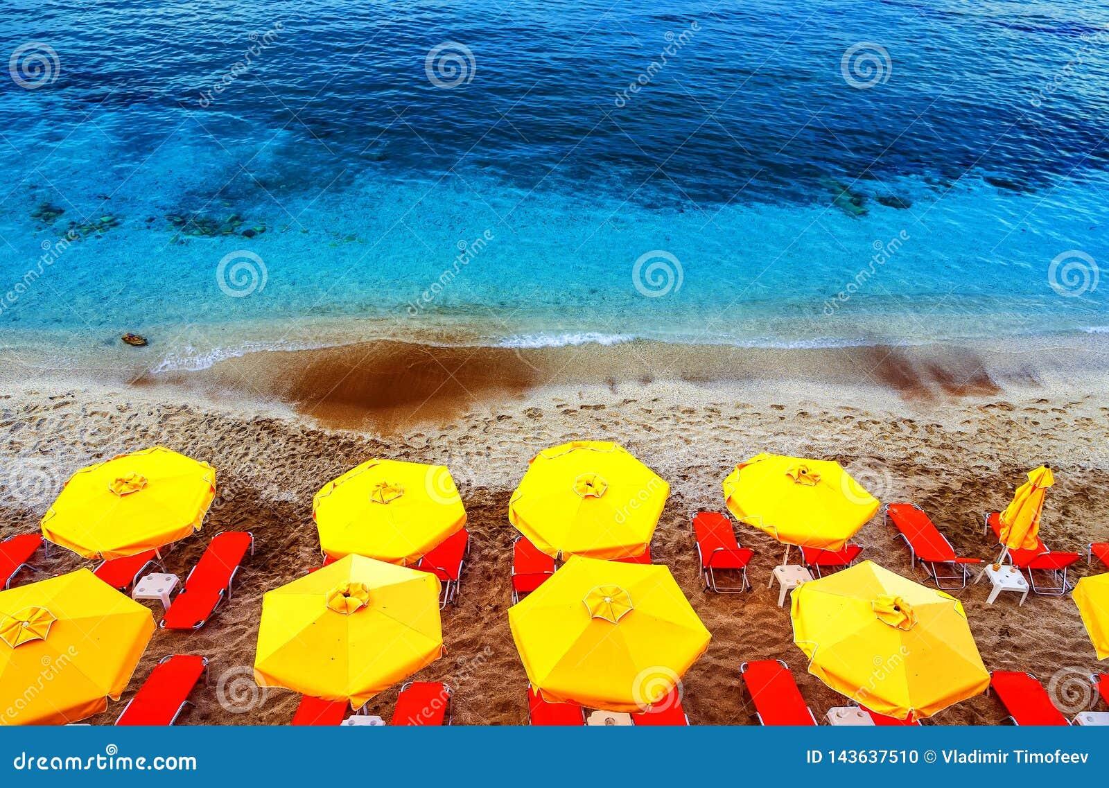 Vue supérieure de chaises et de parapluies de Sun sur la plage blanche rouge multicolore de sable de sable en Crète, Grèce