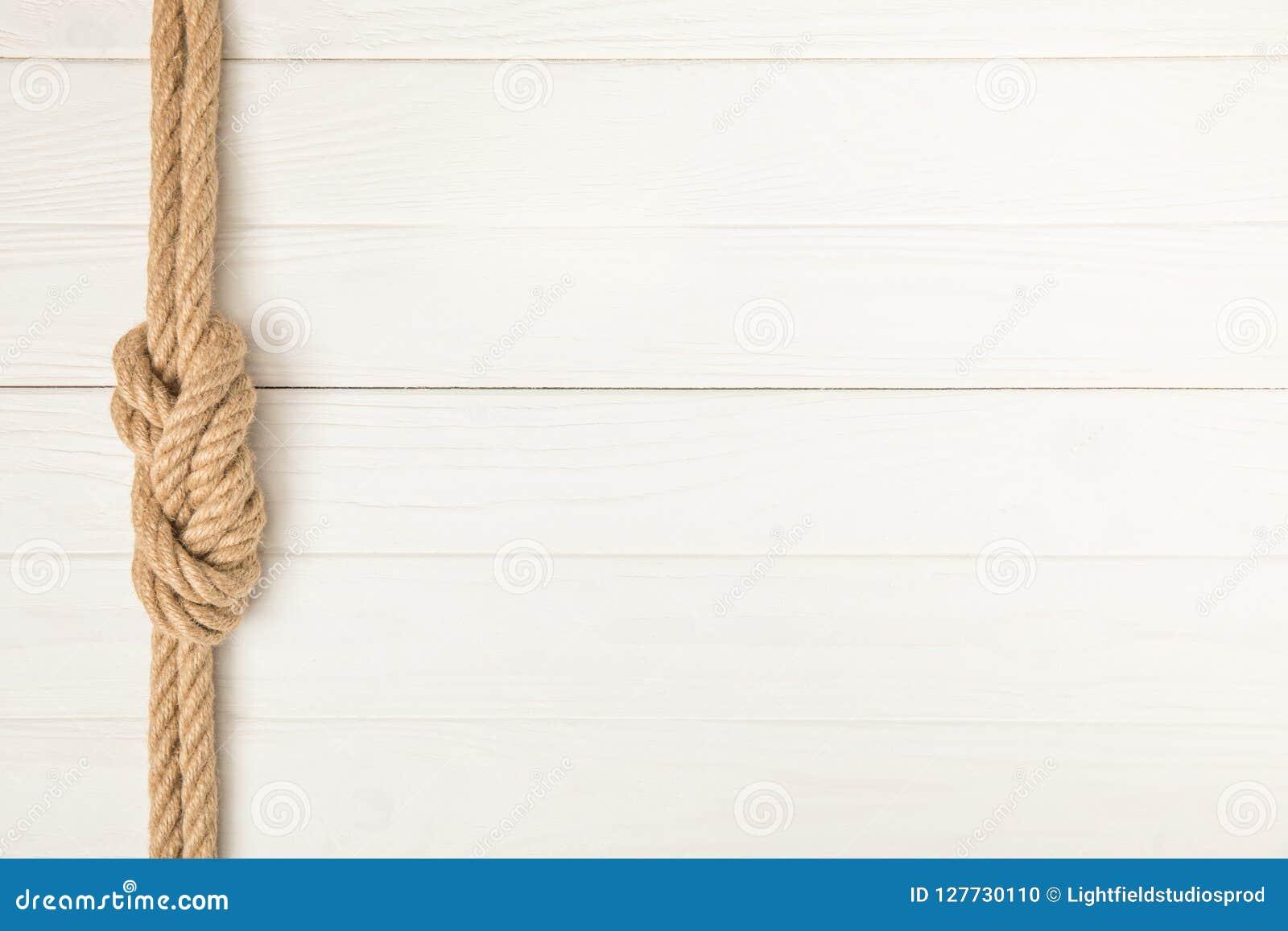 Vue supérieure de corde nautique brune avec le noeud sur la surface en bois blanche