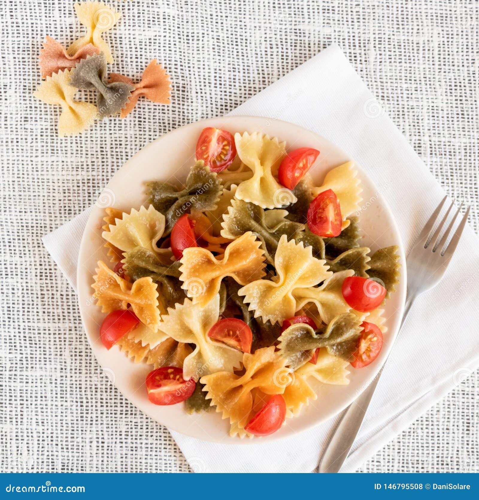 Vue supérieure de farfalle coloré italien de pâtes avec le basilic et les tomates