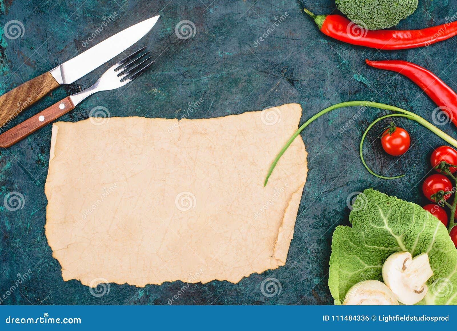 Vue supérieure de parchemin vide, de fourchette avec le couteau et de légumes crus mûrs