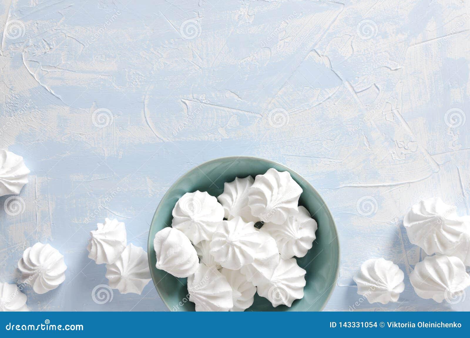 Vue supérieure de plat bleu complètement des meringues croustillantes sur la table lumineuse Copiez le For Your Information de l