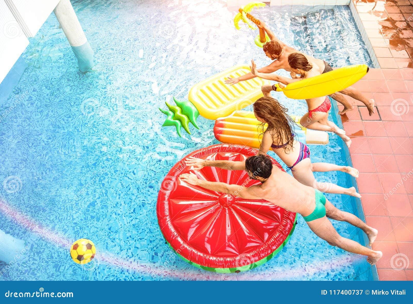 Vue supérieure des amis actifs sautant à la réception au bord de la piscine de natation - Vaca